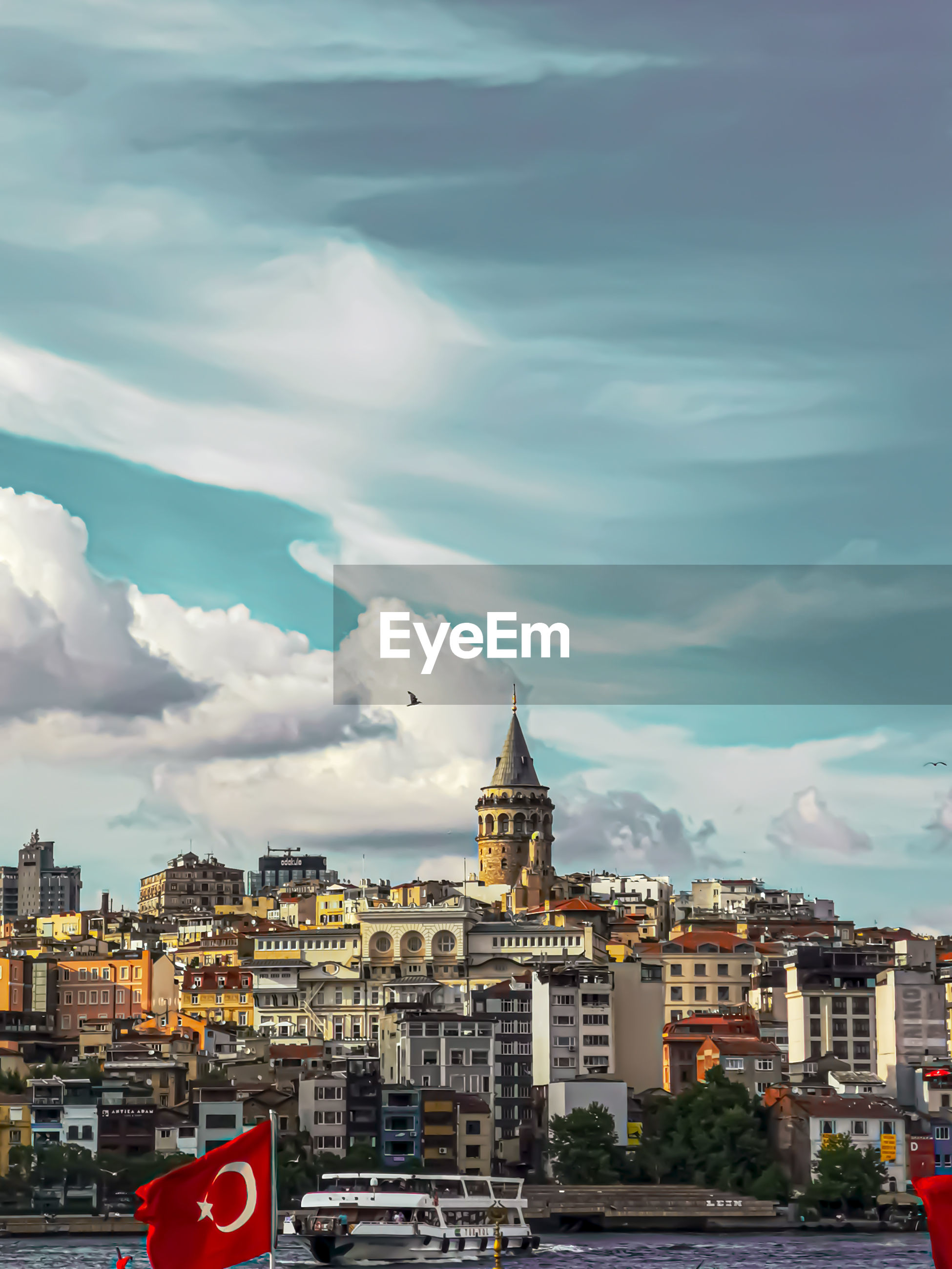 City crowd against cloudy sky in istanbul in front of galata tower in eminönü
