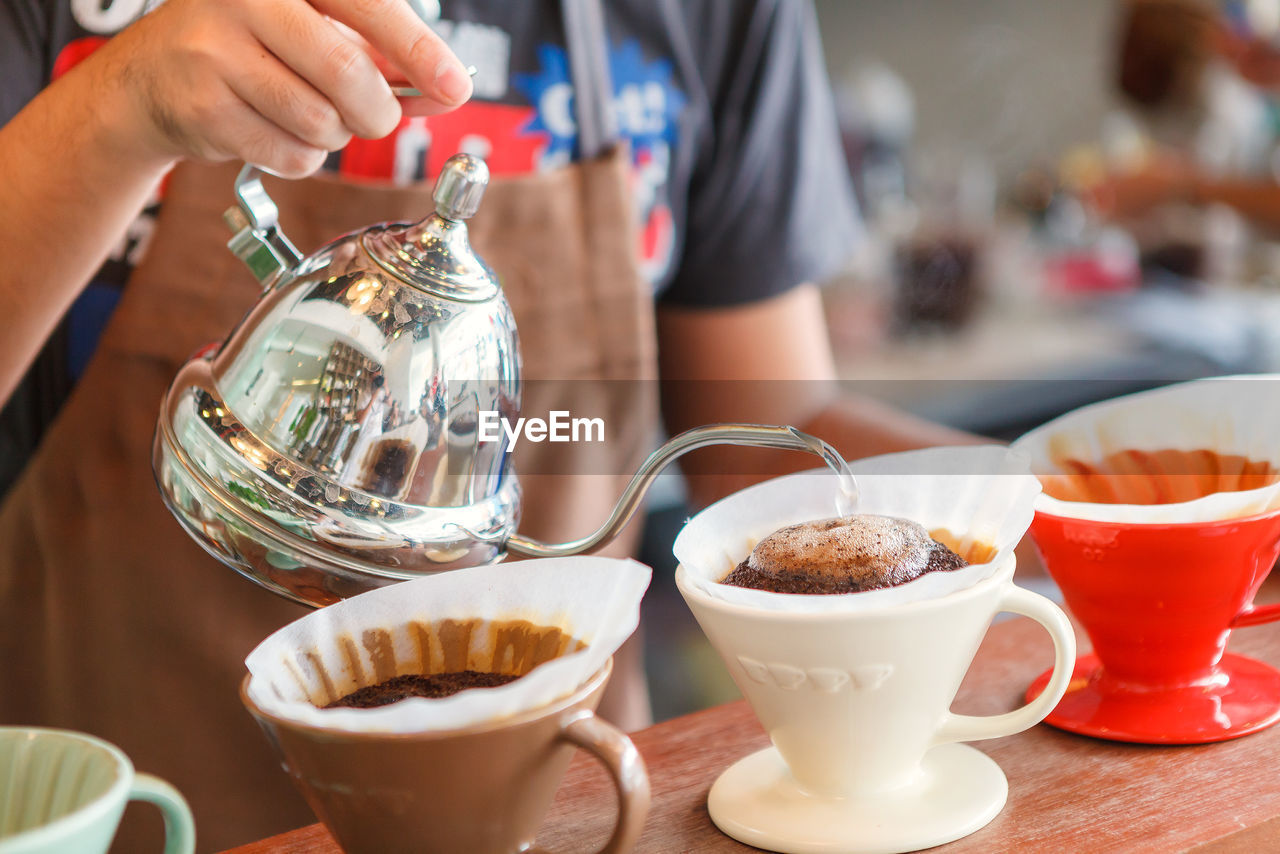 Close-Up Of Hand Holding Pouring Coffee In Cups On Table