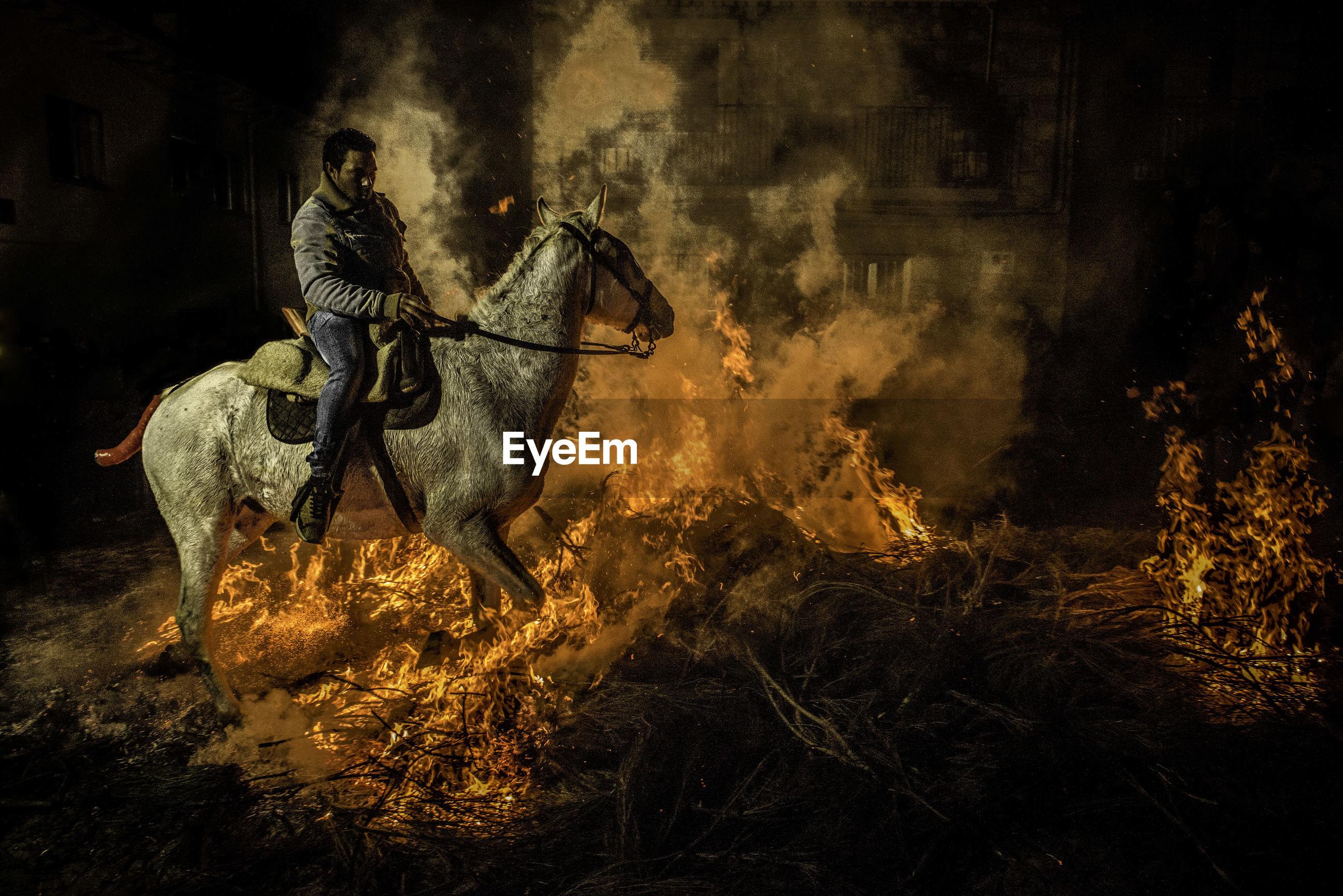 FULL LENGTH OF MAN HOLDING FIRE