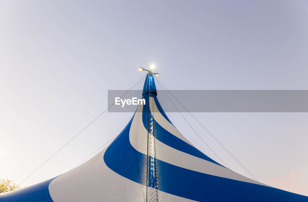 Low Angle View Of Illuminated Lights On Striped Circus Tent Against Sky