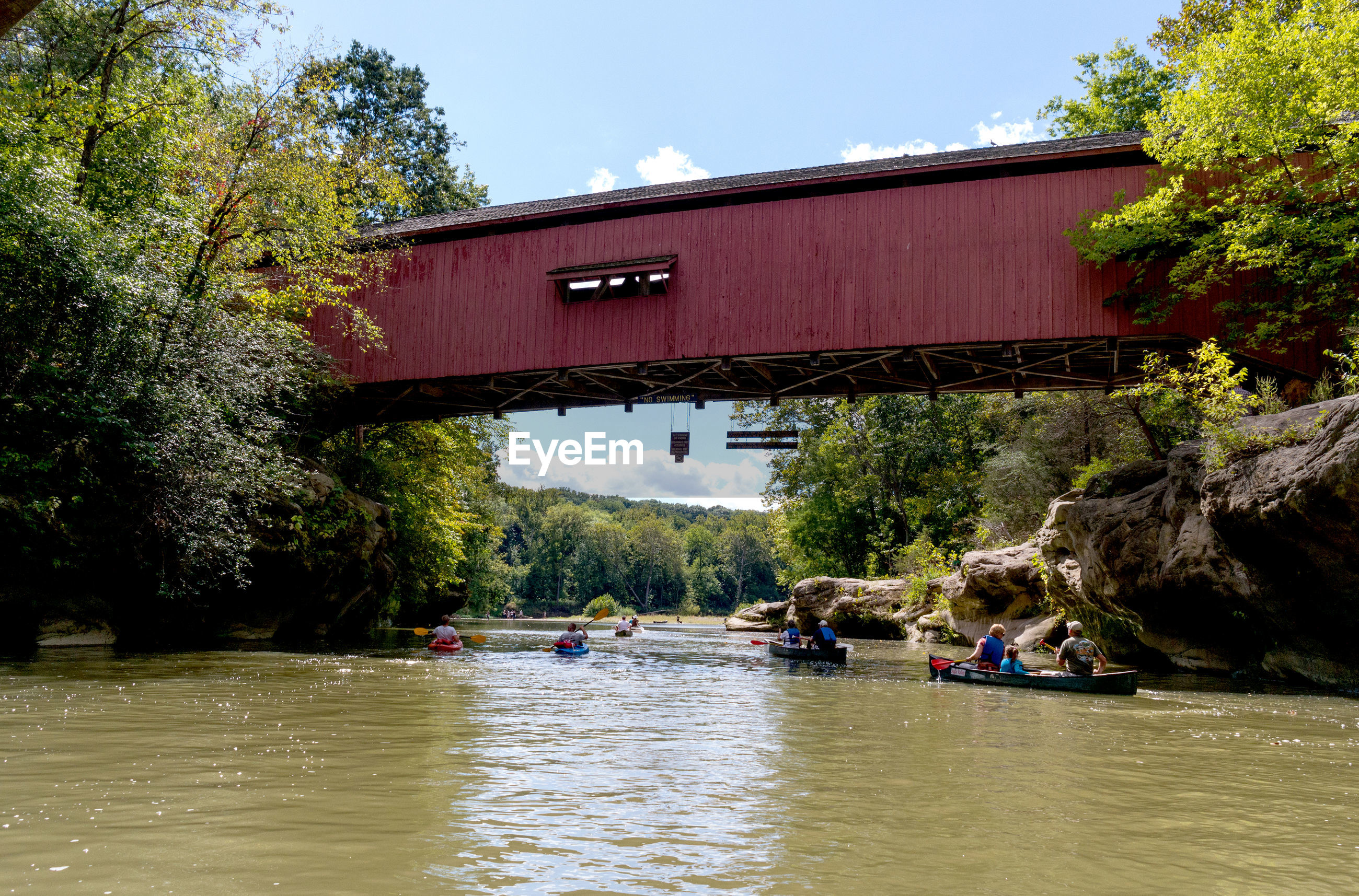 Tourists in rowboats and kayacks float under a covered bridge in southern indiana