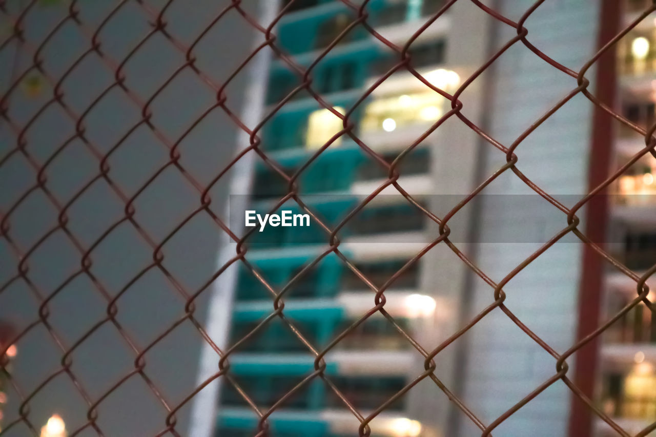 Low angle view of building seen through chainlink fence