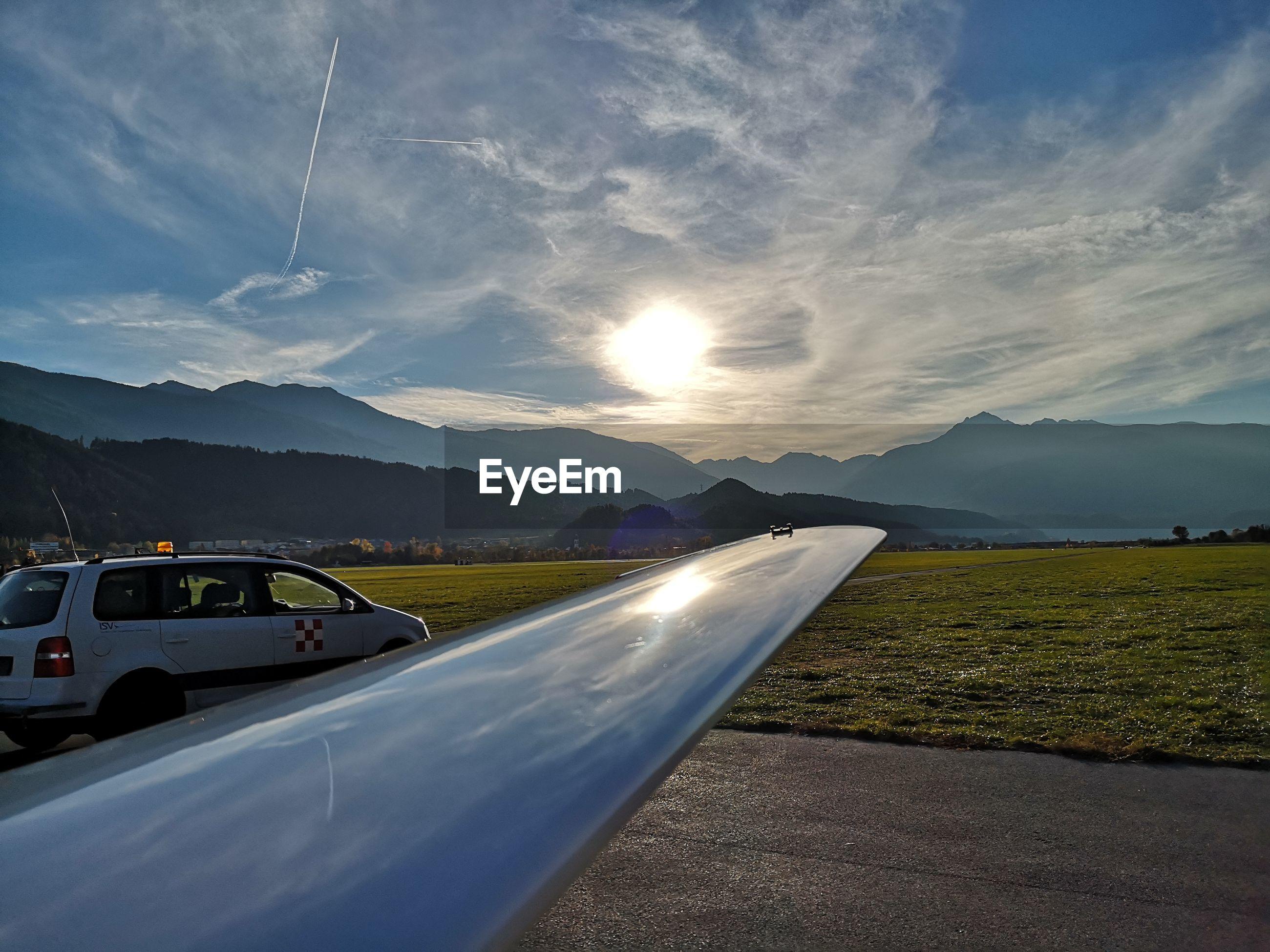 CAR ON MOUNTAINS AGAINST SKY