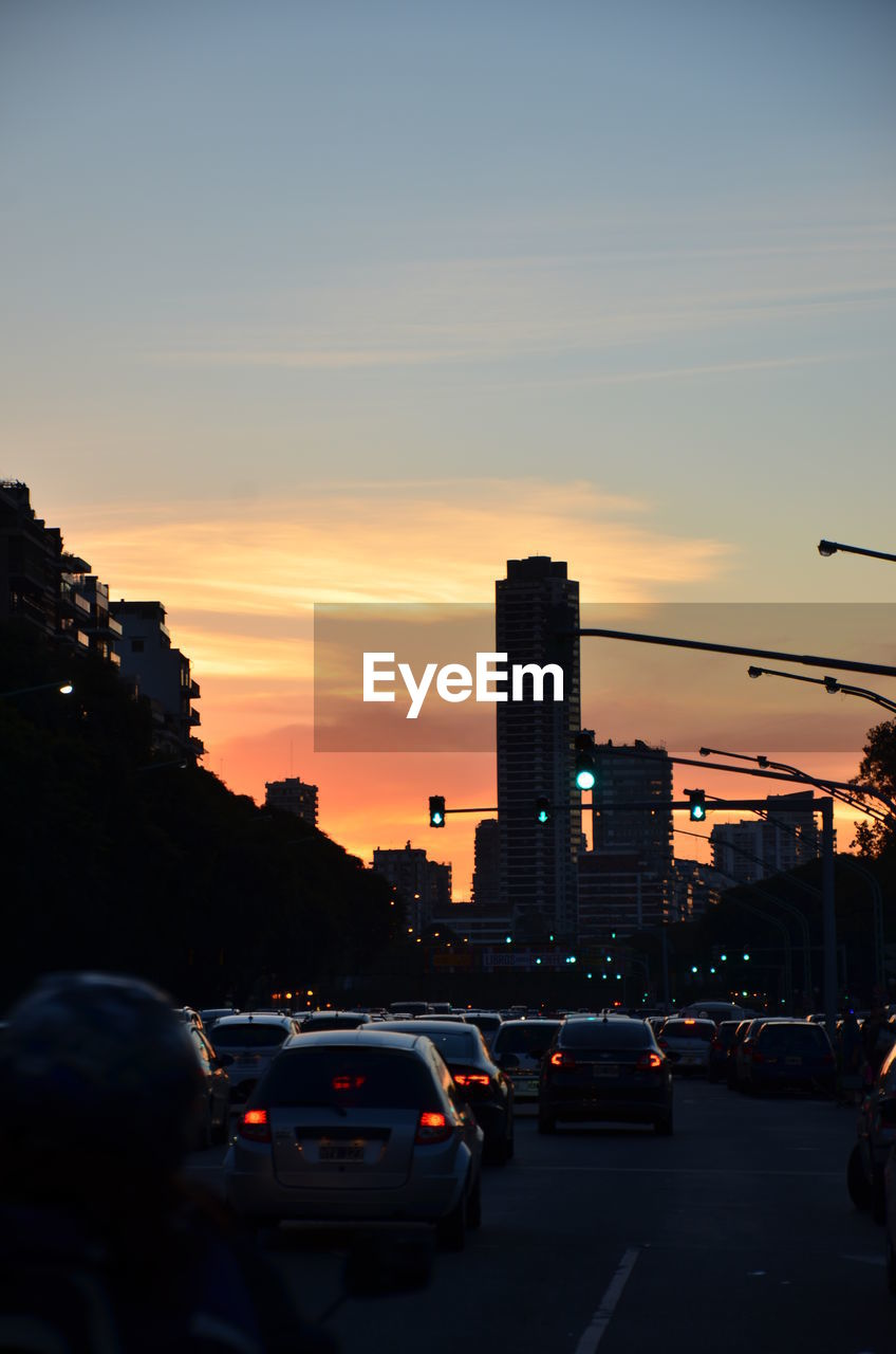 Cars parked in traffic amidst silhouette buildings against sky during sunset