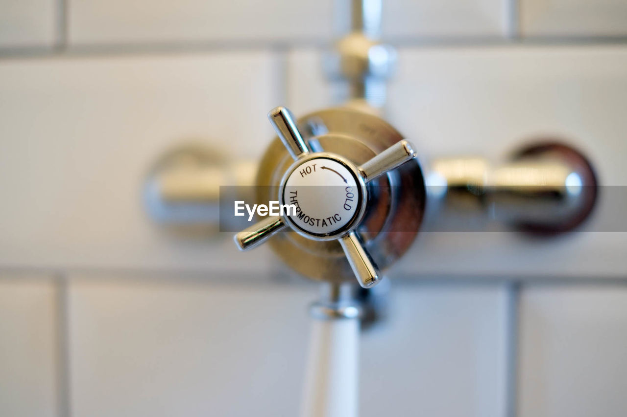 Close-up of knob on wall in bathroom