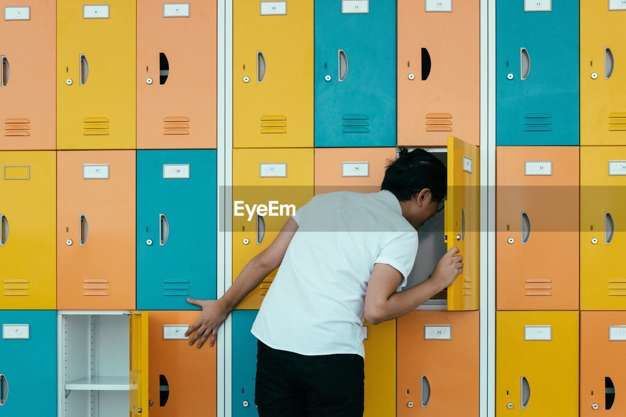 Rear View Of Young Man Looking In Lockers