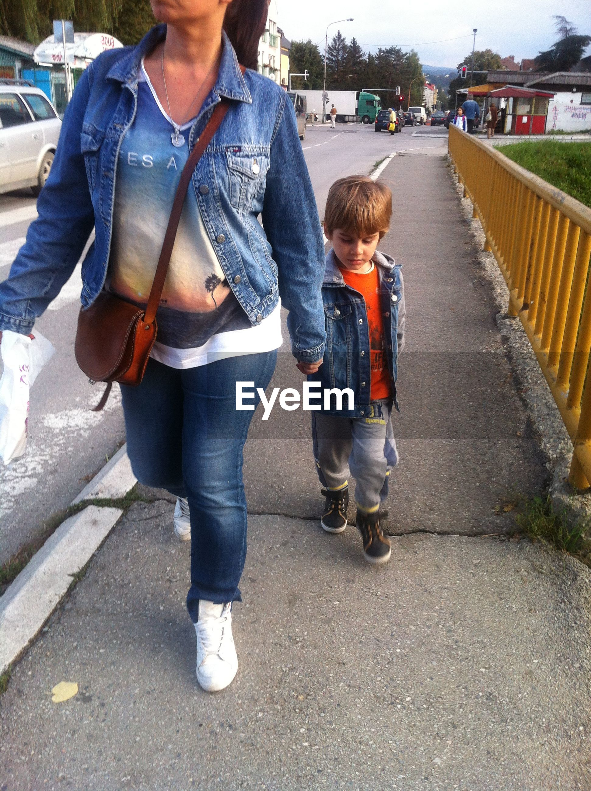 Low section of mother with son holding hands while walking on footpath in city