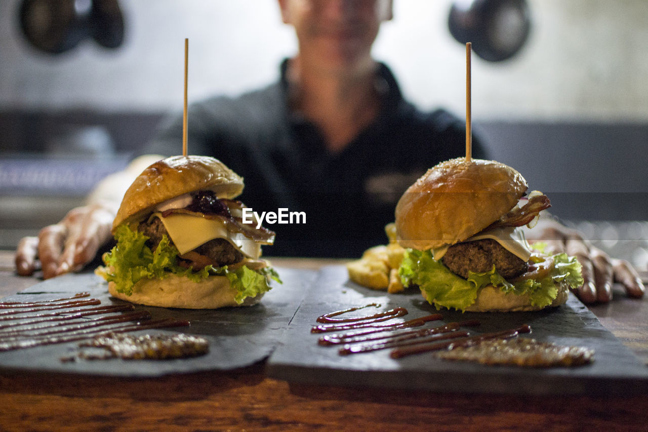 Midsection Of Mature Woman With Burgers On Table In Cafe