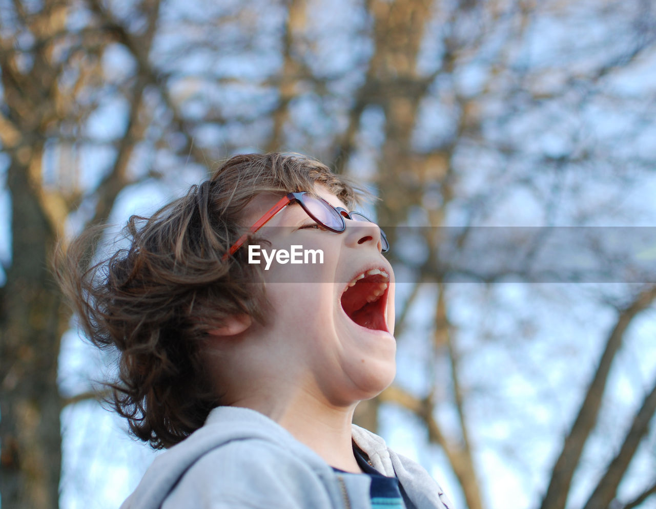 Close-Up Of Boy Screaming While Standing Against Bare Trees