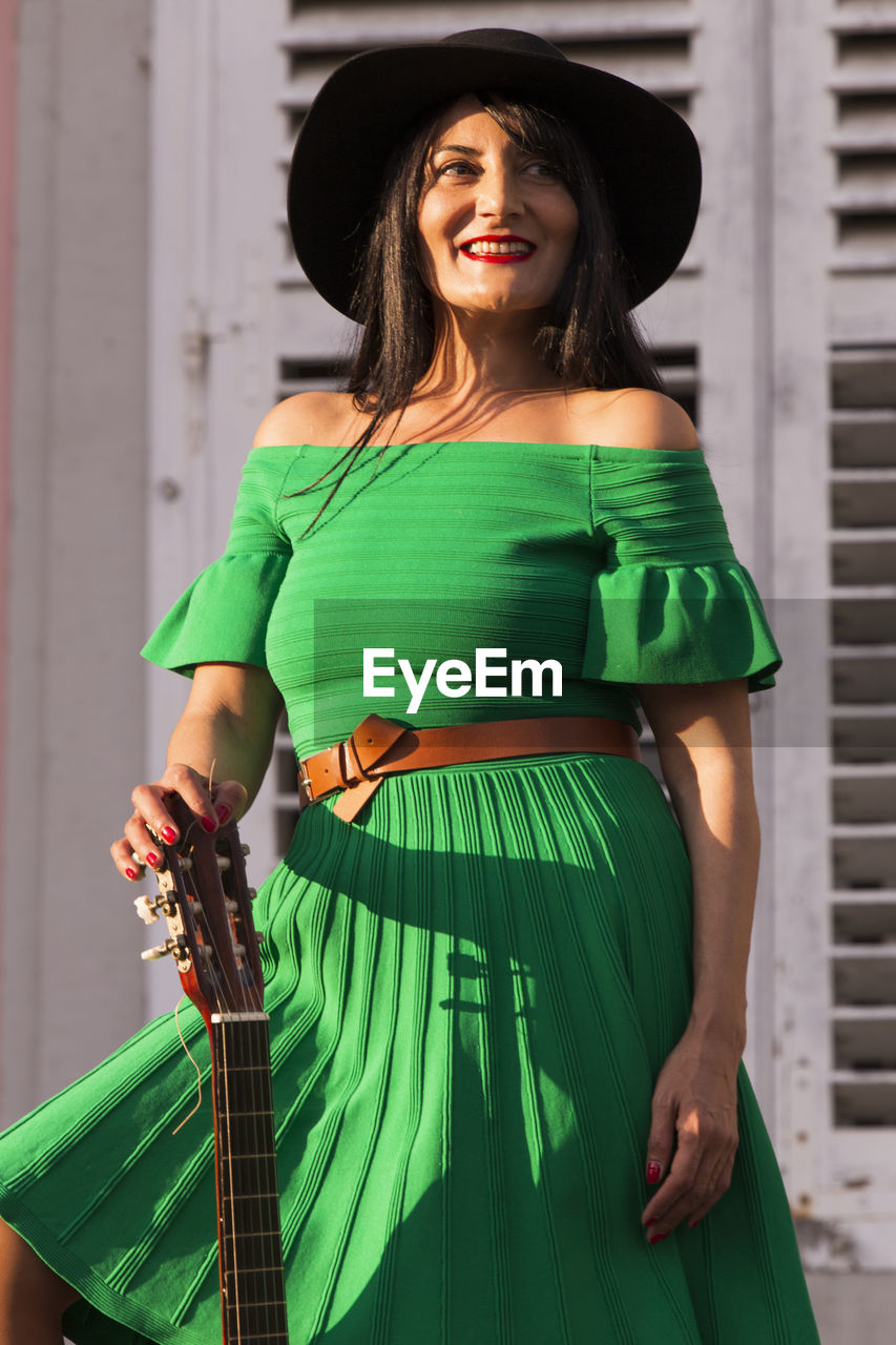 hat, one person, clothing, real people, green color, three quarter length, standing, women, front view, portrait, young adult, lifestyles, musical instrument, adult, leisure activity, holding, arts culture and entertainment, string instrument, young women, fashion, beautiful woman, hairstyle