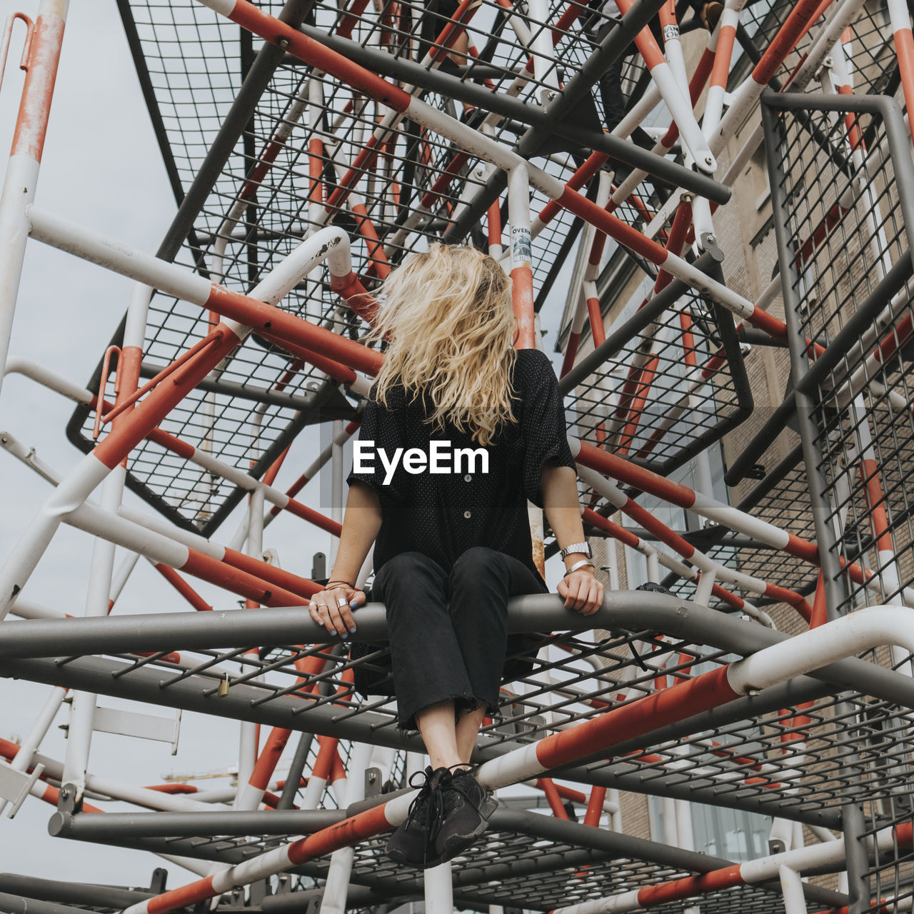 Woman Sitting On Built Structure Against Sky