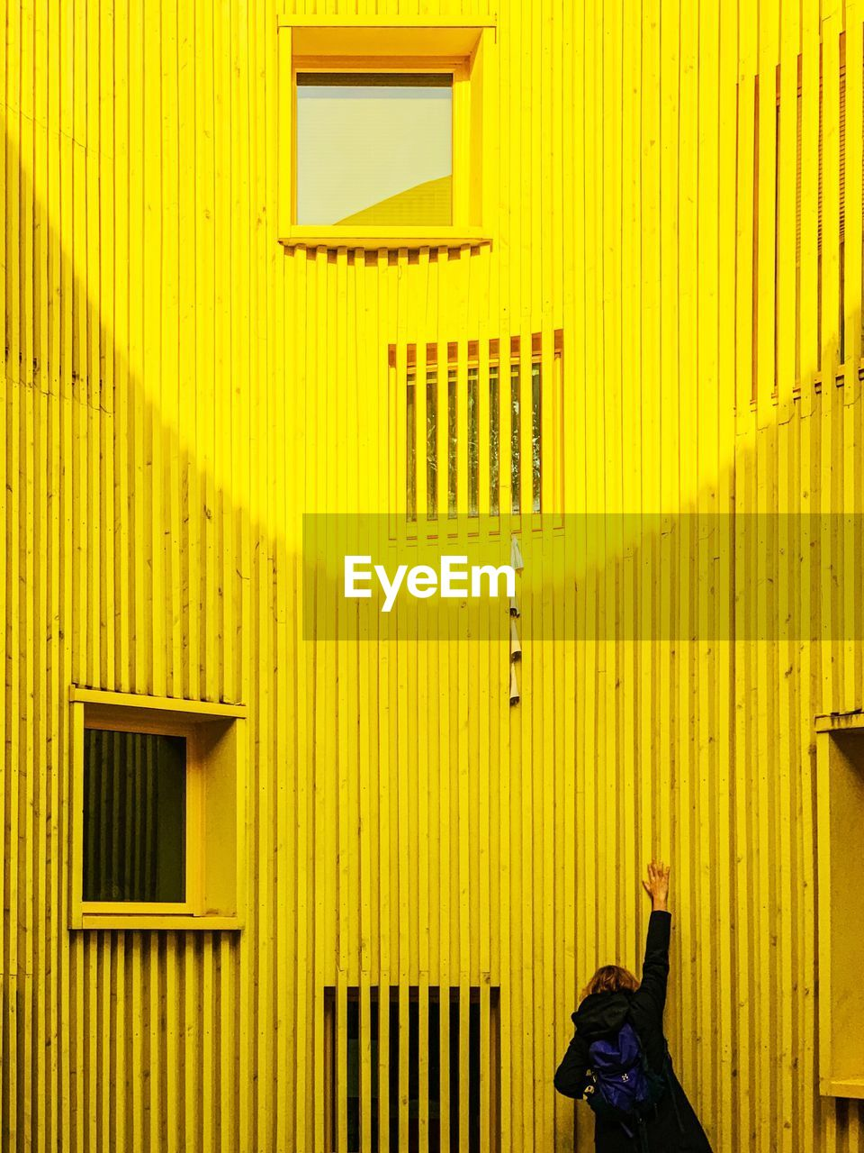yellow, architecture, built structure, building exterior, real people, one person, building, lifestyles, day, window, leisure activity, wall - building feature, outdoors, standing, women, clothing, pattern, wood - material, unrecognizable person, iron