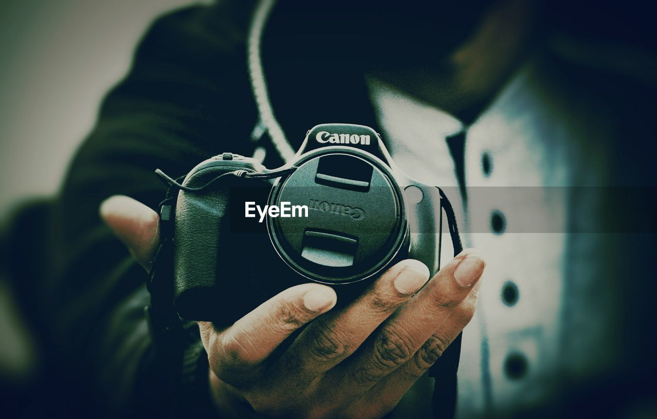 human hand, hand, technology, human body part, one person, real people, holding, focus on foreground, close-up, photographic equipment, lifestyles, camera - photographic equipment, midsection, photography themes, men, modern, digital camera, camera, leisure activity, finger, photographer, slr camera
