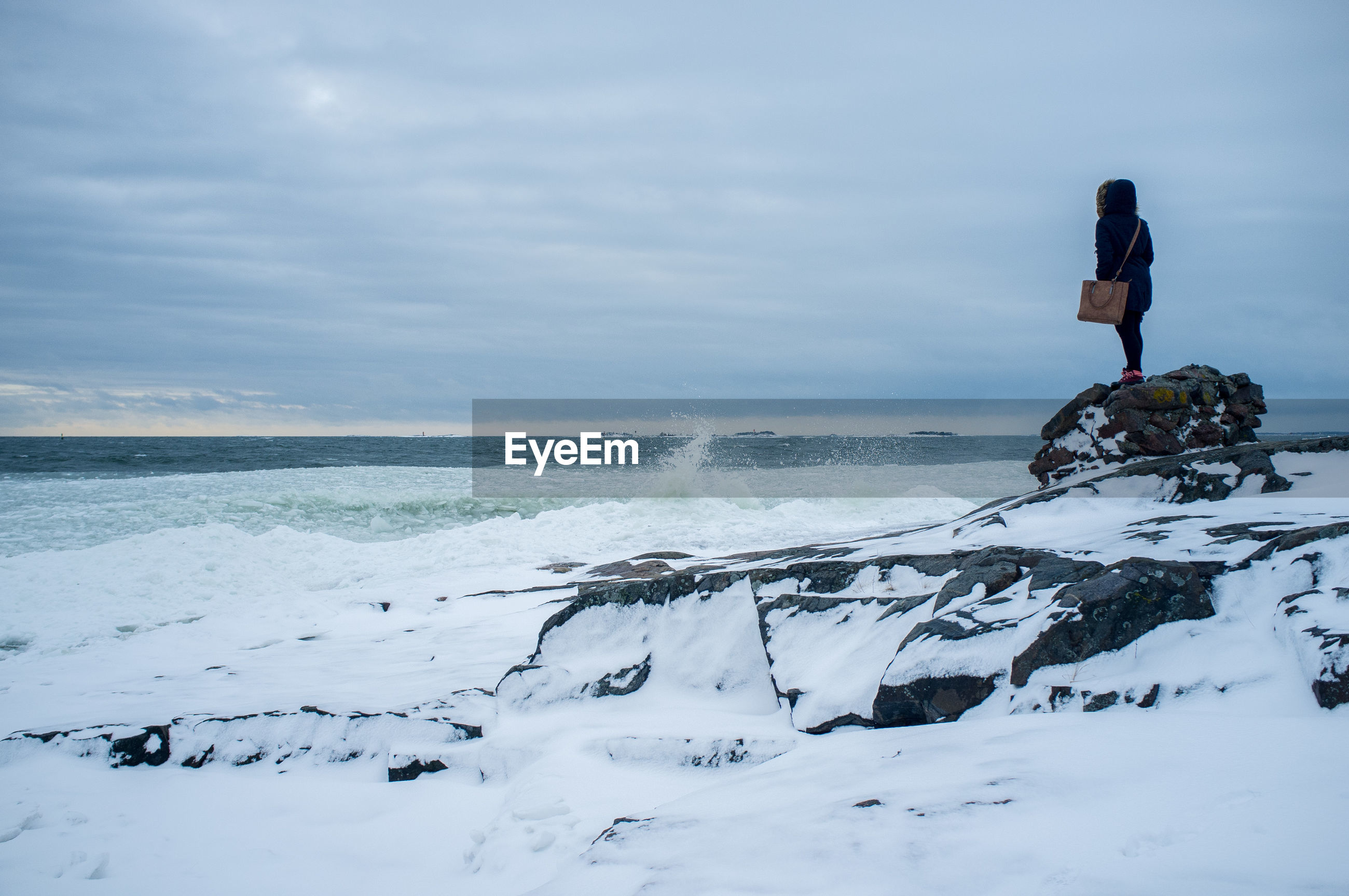 Woman standing on rock on snow covered beach