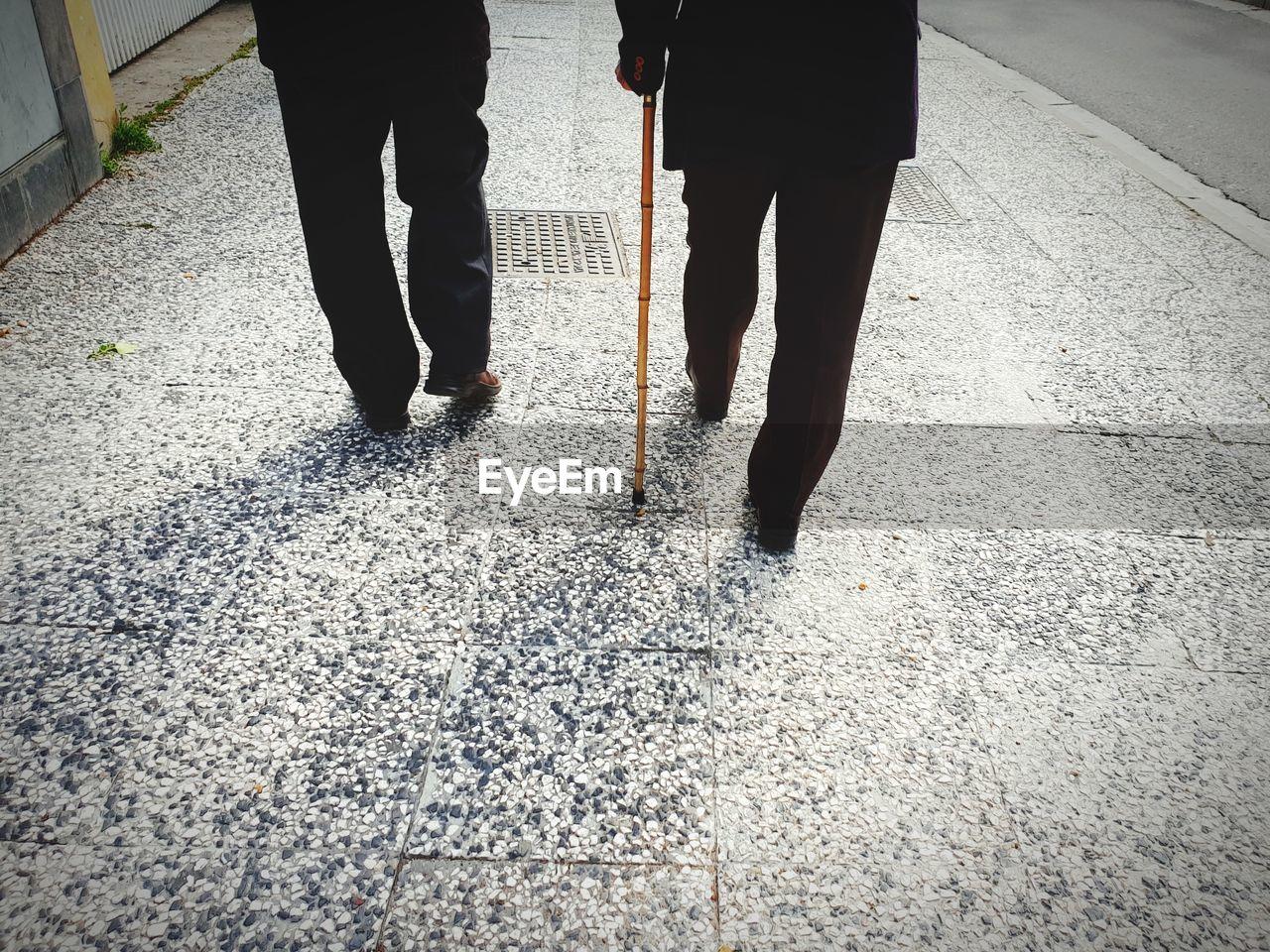 Low section of men walking on sidewalk