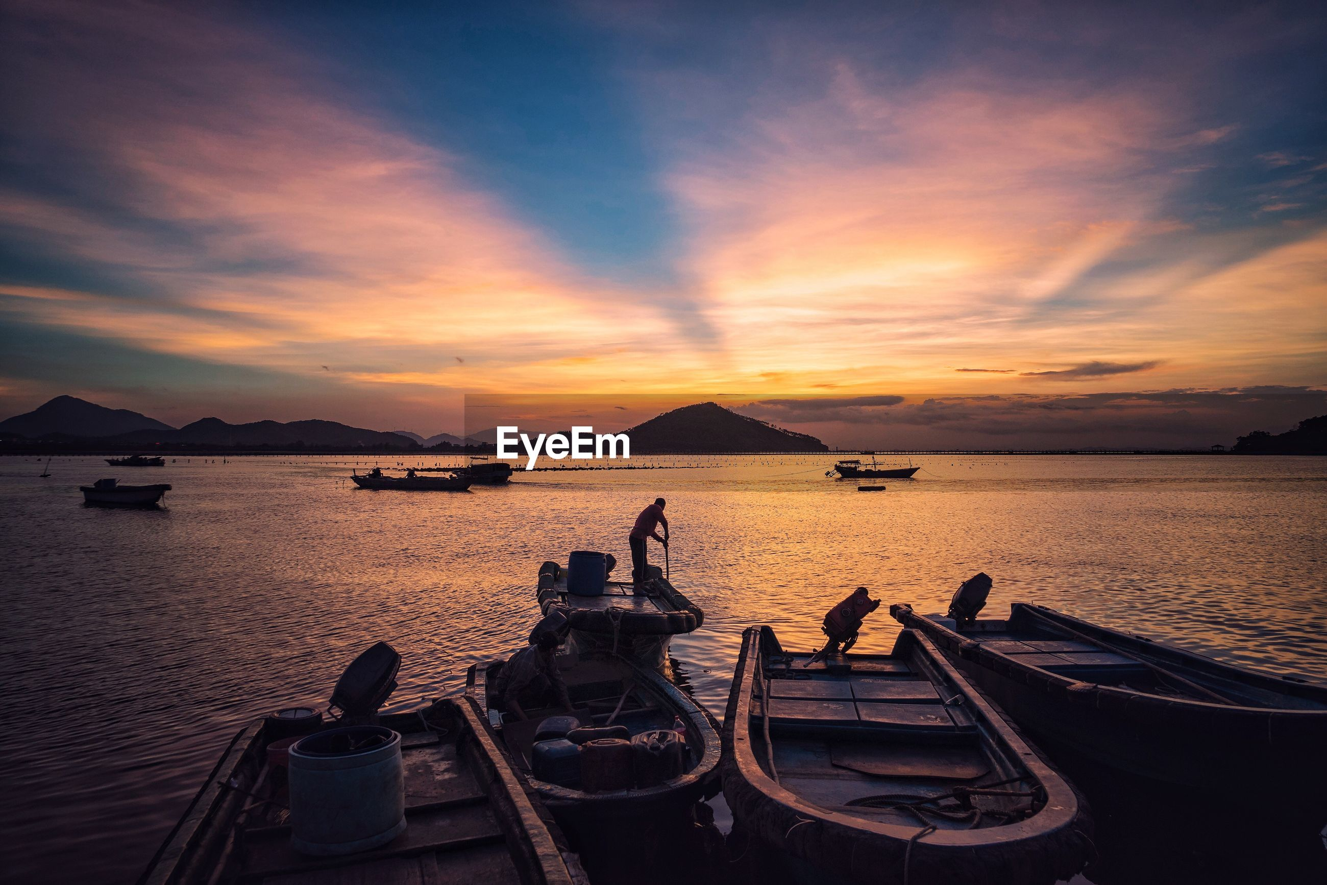 Man in boat on sea against sky during sunset