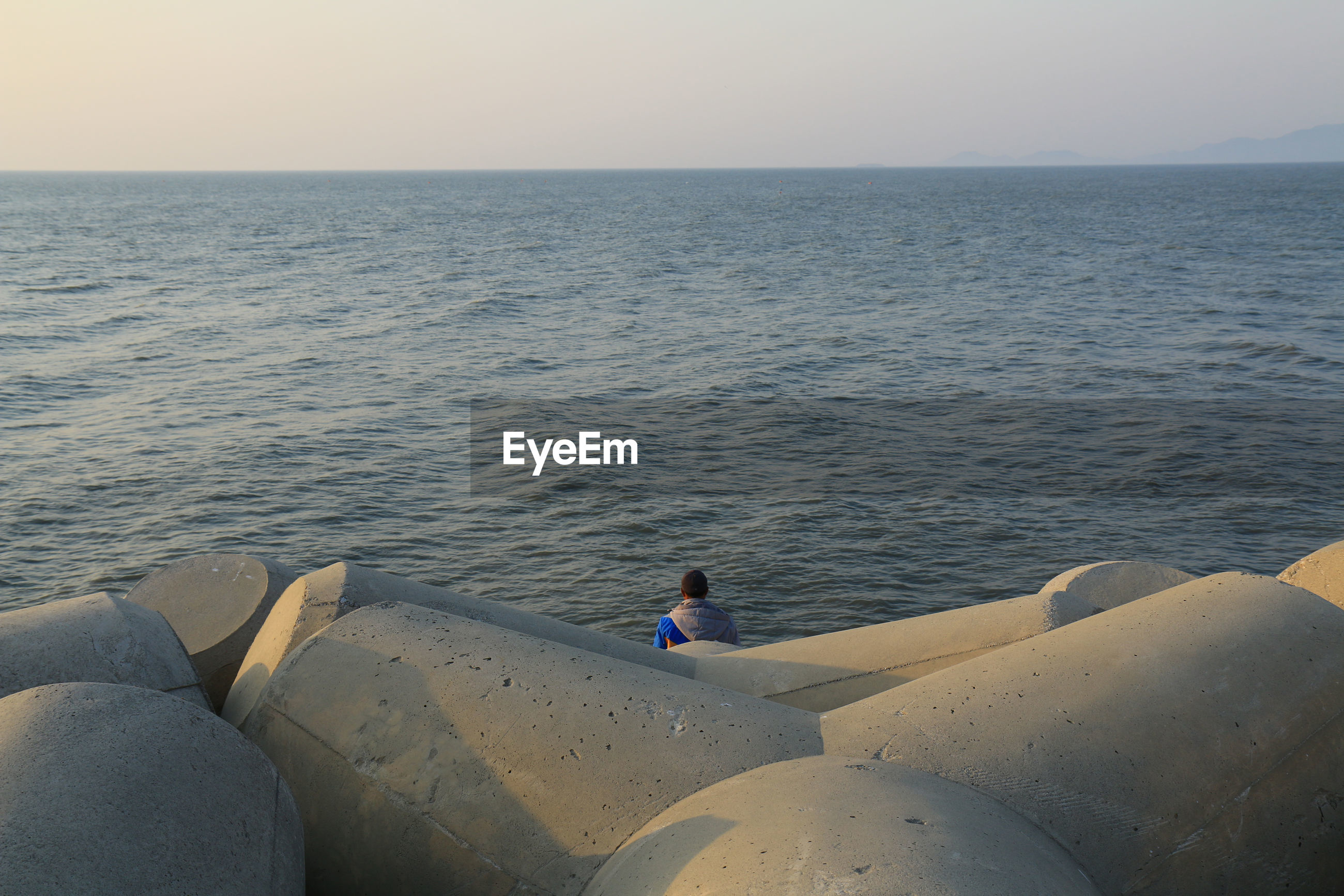 High angle view of man by tetrapod rocks against sea