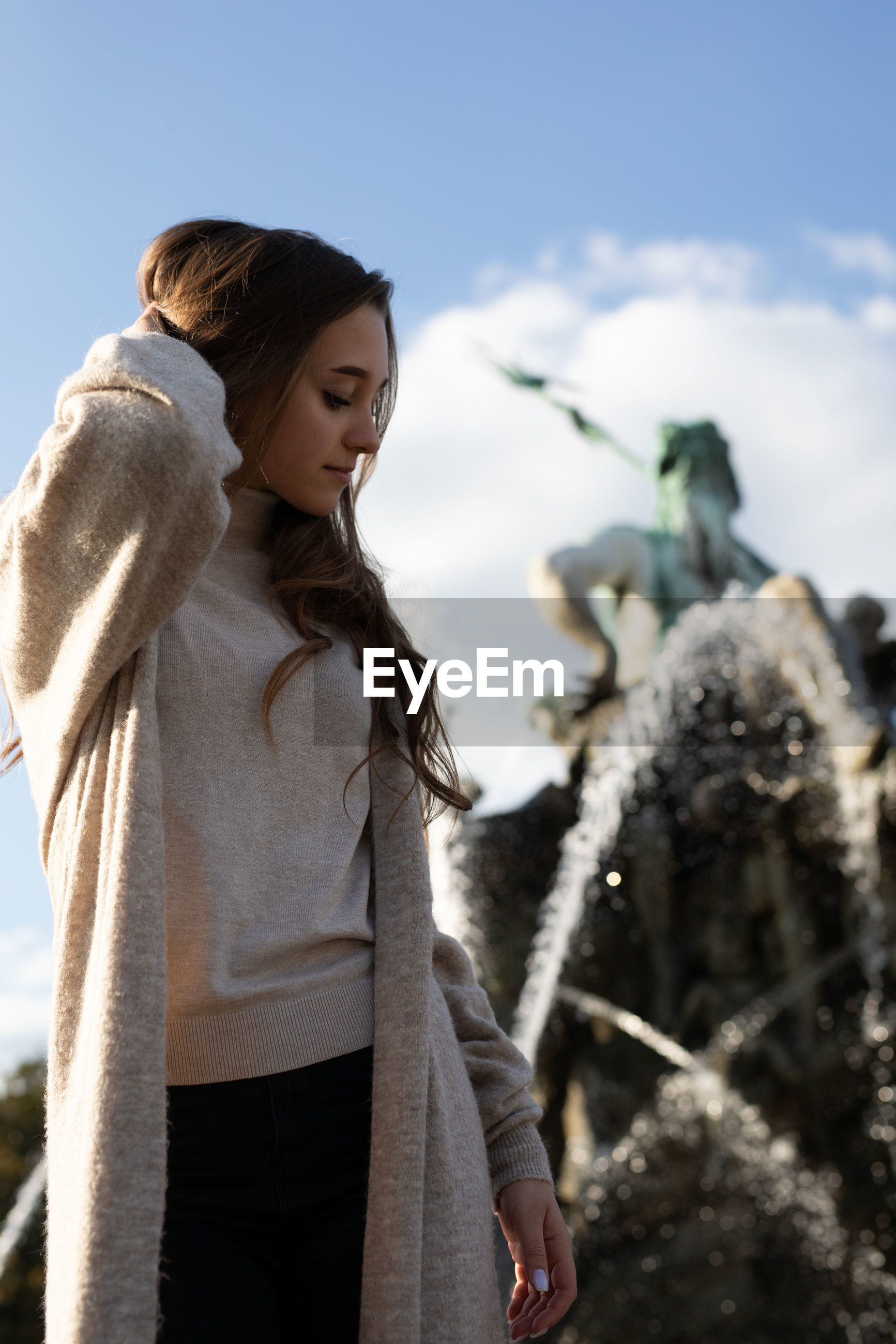 Young woman standing fountain in city
