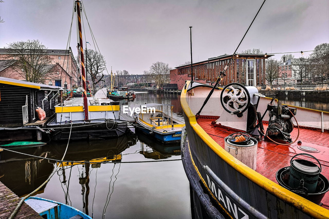 BOATS MOORED IN CANAL AGAINST SKY