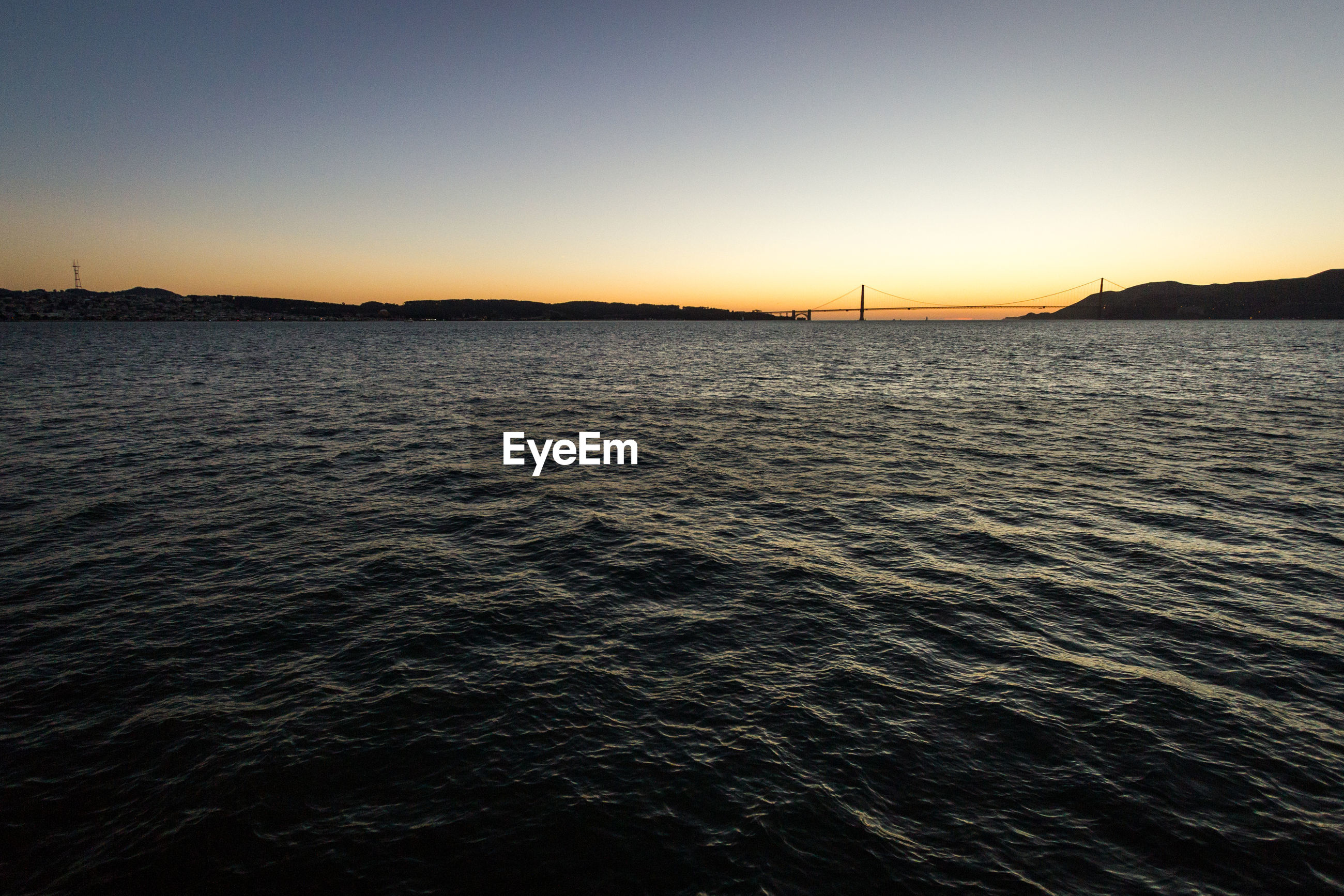 SCENIC VIEW OF SEA AGAINST CLEAR SKY AT DUSK