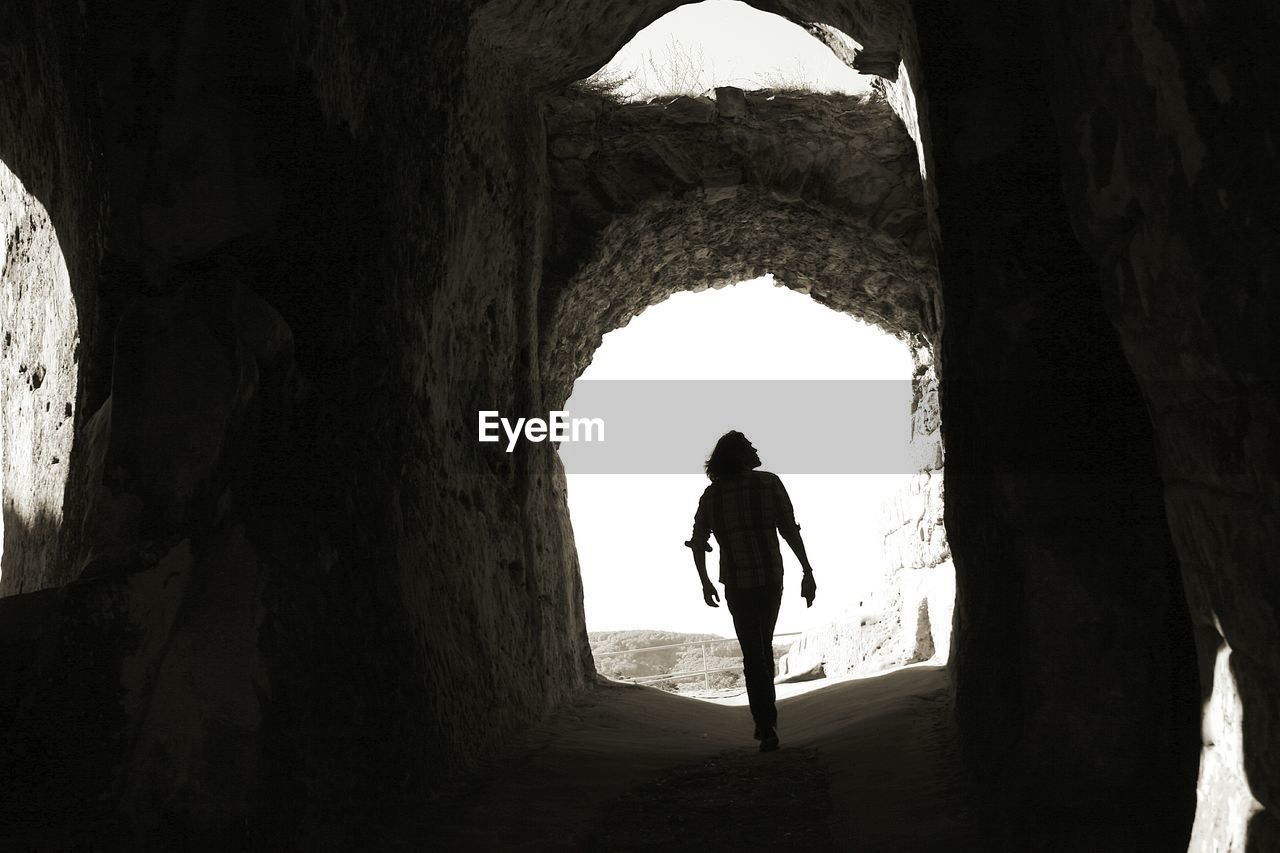 real people, architecture, full length, arch, one person, lifestyles, leisure activity, standing, day, silhouette, rear view, indoors, men, history, cave, the past, built structure, nature, rock formation, light at the end of the tunnel