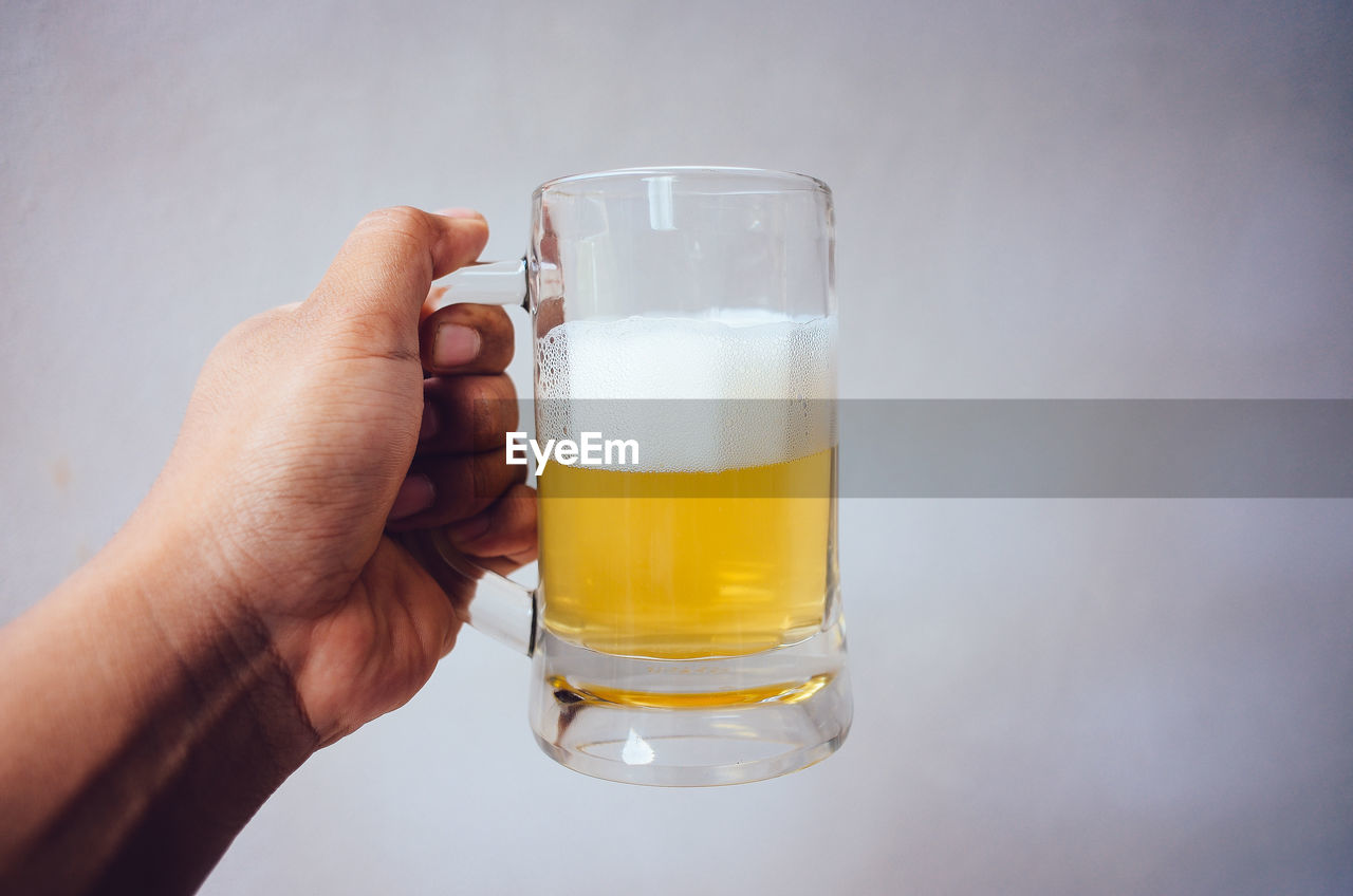 refreshment, human hand, drink, human body part, hand, holding, food and drink, one person, glass, drinking glass, body part, household equipment, real people, freshness, lifestyles, beer, close-up, unrecognizable person, focus on foreground, beer - alcohol, finger, human limb