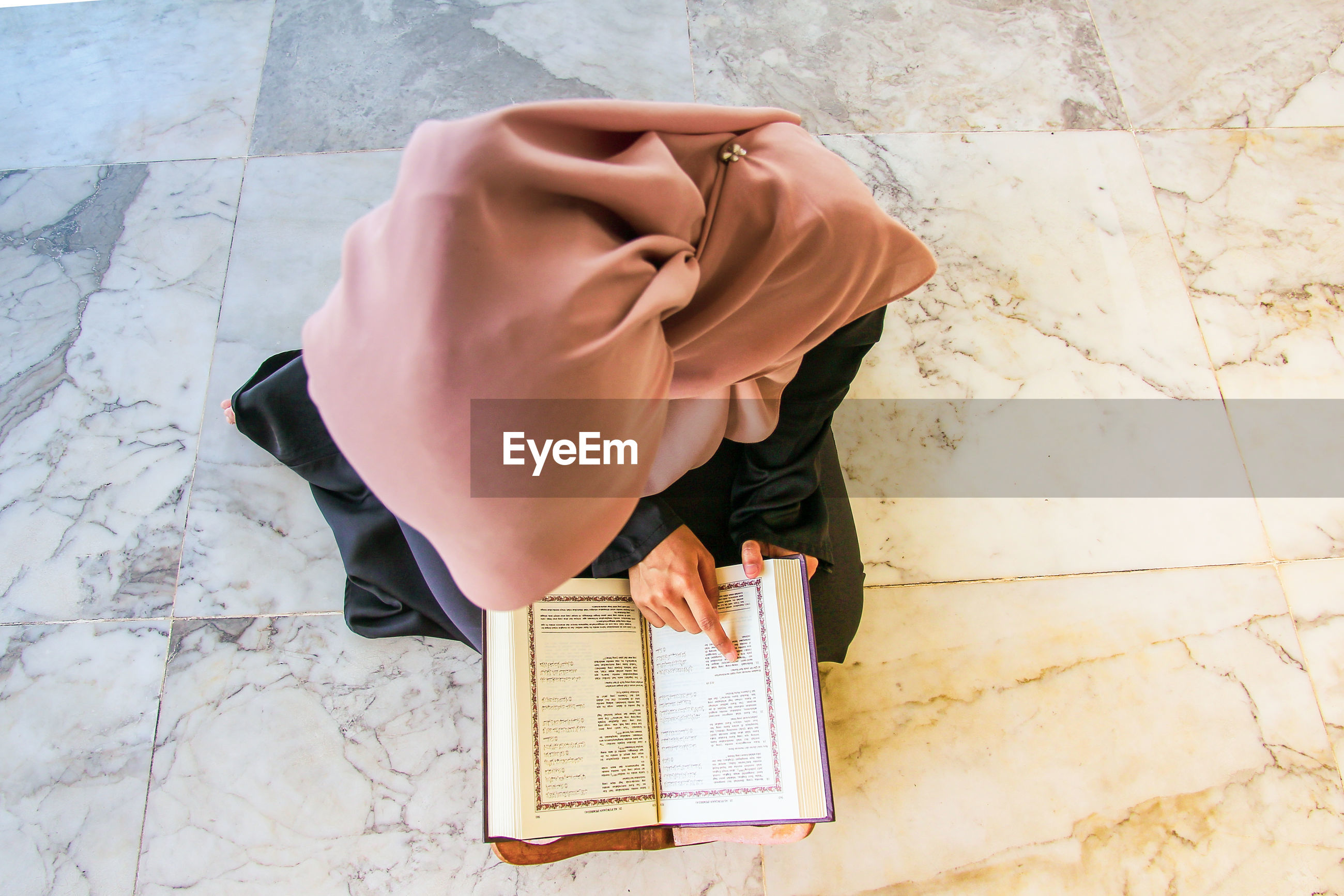 High angle view of young woman reading holy book while sitting at mosque
