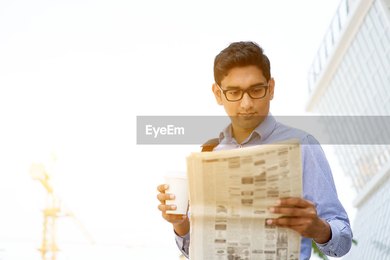 eyeglasses, one person, young adult, glasses, holding, young men, front view, activity, reading, paper, newspaper, waist up, real people, built structure, men, copy space, lifestyles, males