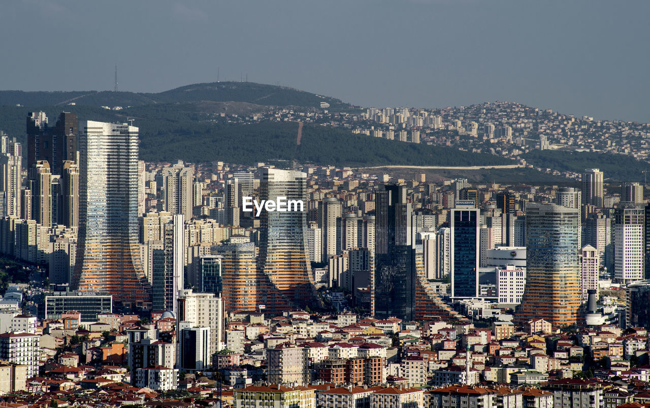 building exterior, architecture, city, cityscape, built structure, building, office building exterior, skyscraper, residential district, sky, crowded, crowd, modern, city life, mountain, tall - high, nature, landscape, high angle view, outdoors, apartment, financial district