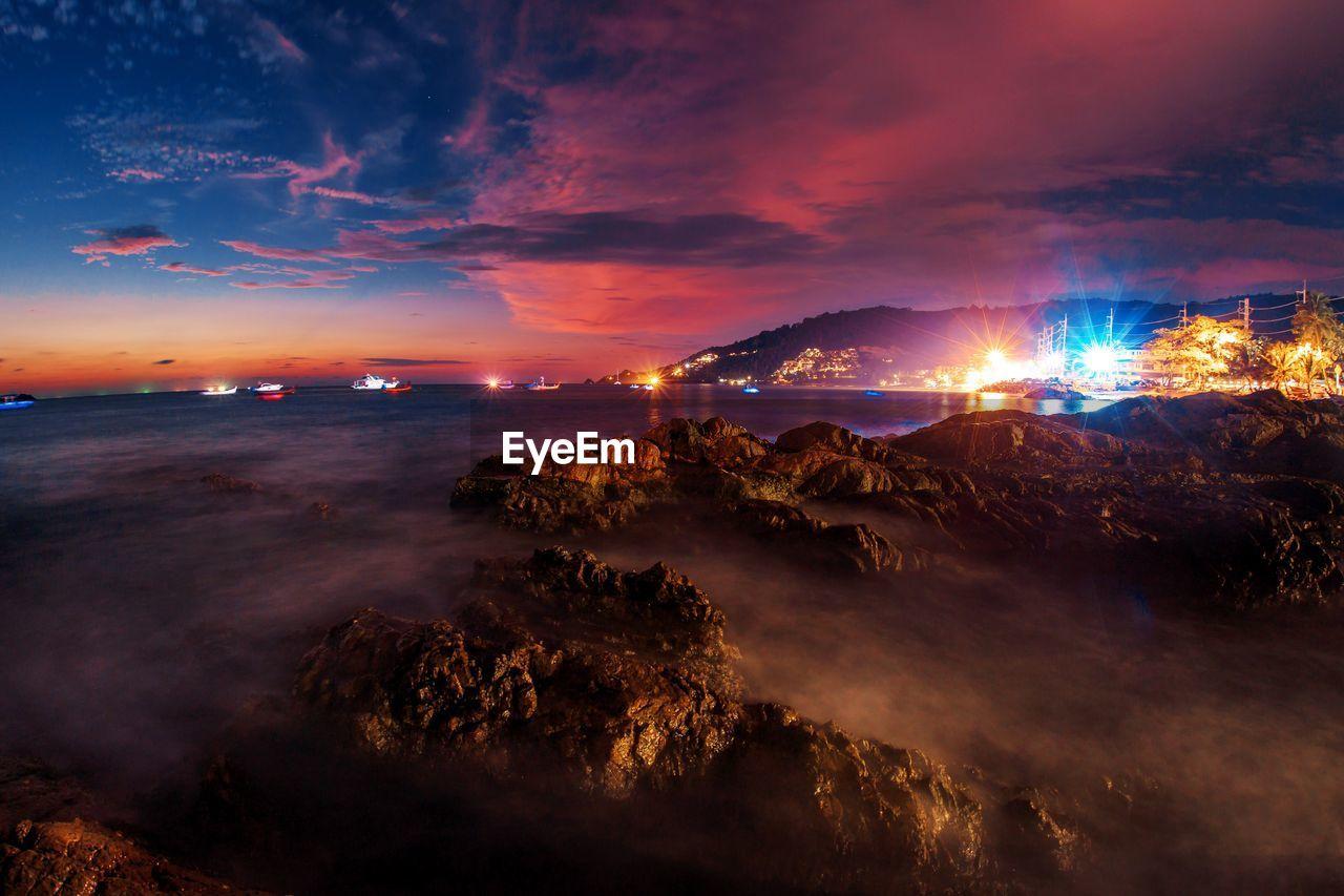 sky, cloud - sky, beauty in nature, scenics - nature, water, sea, illuminated, nature, no people, tranquil scene, tranquility, sunset, night, land, idyllic, non-urban scene, mountain, orange color, travel destinations