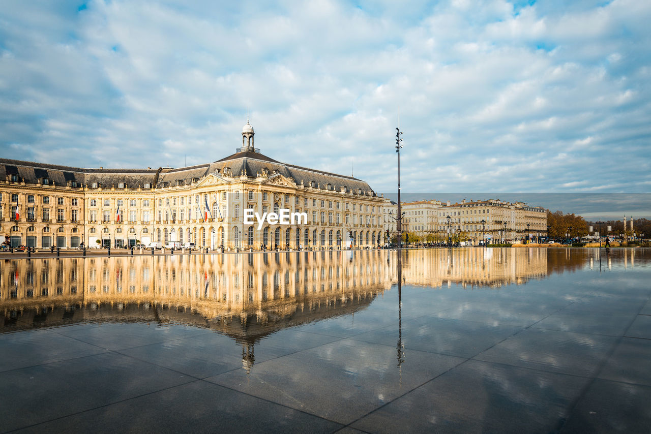 Reflection Of Old Building In Lake Water Against Cloudy Sky