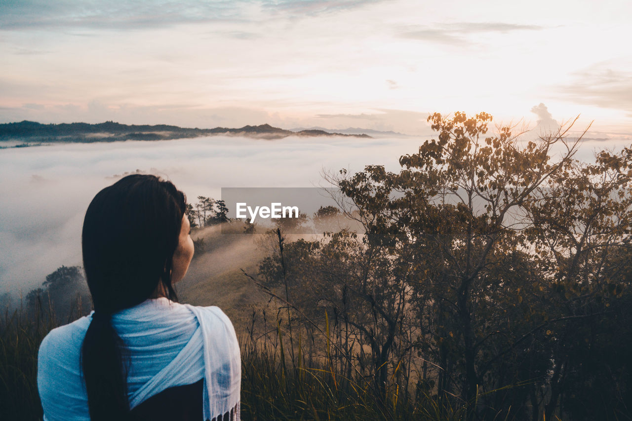 Rear View Of Woman Looking At Foggy Landscape During Sunset