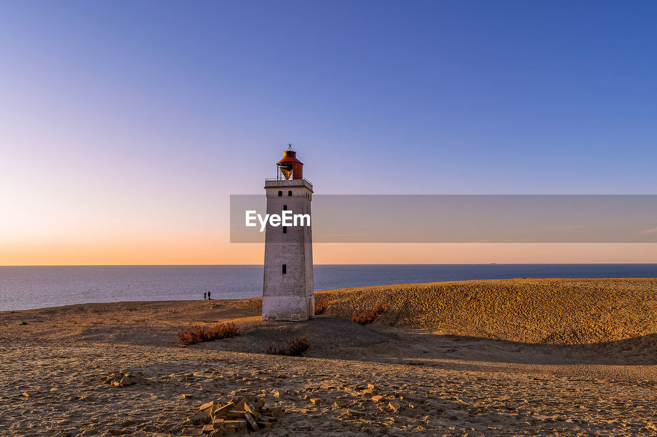 LIGHTHOUSE BY SEA AGAINST CLEAR SKY AT SUNSET
