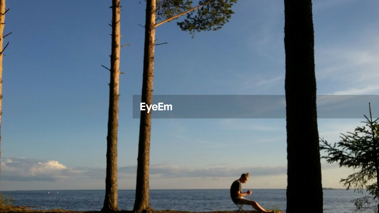 sea, water, sky, nature, one person, tree trunk, leisure activity, tree, real people, standing, horizon over water, scenics, beauty in nature, outdoors, day, rope swing, people
