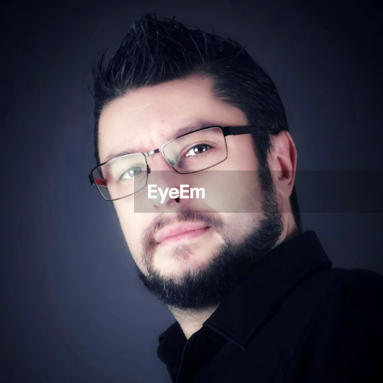 PORTRAIT OF YOUNG MAN WITH EYEGLASSES AGAINST BLACK BACKGROUND