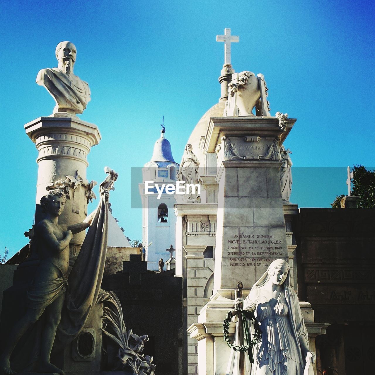 Low angle view of statues against clear blue sky at la recoleta cemetery
