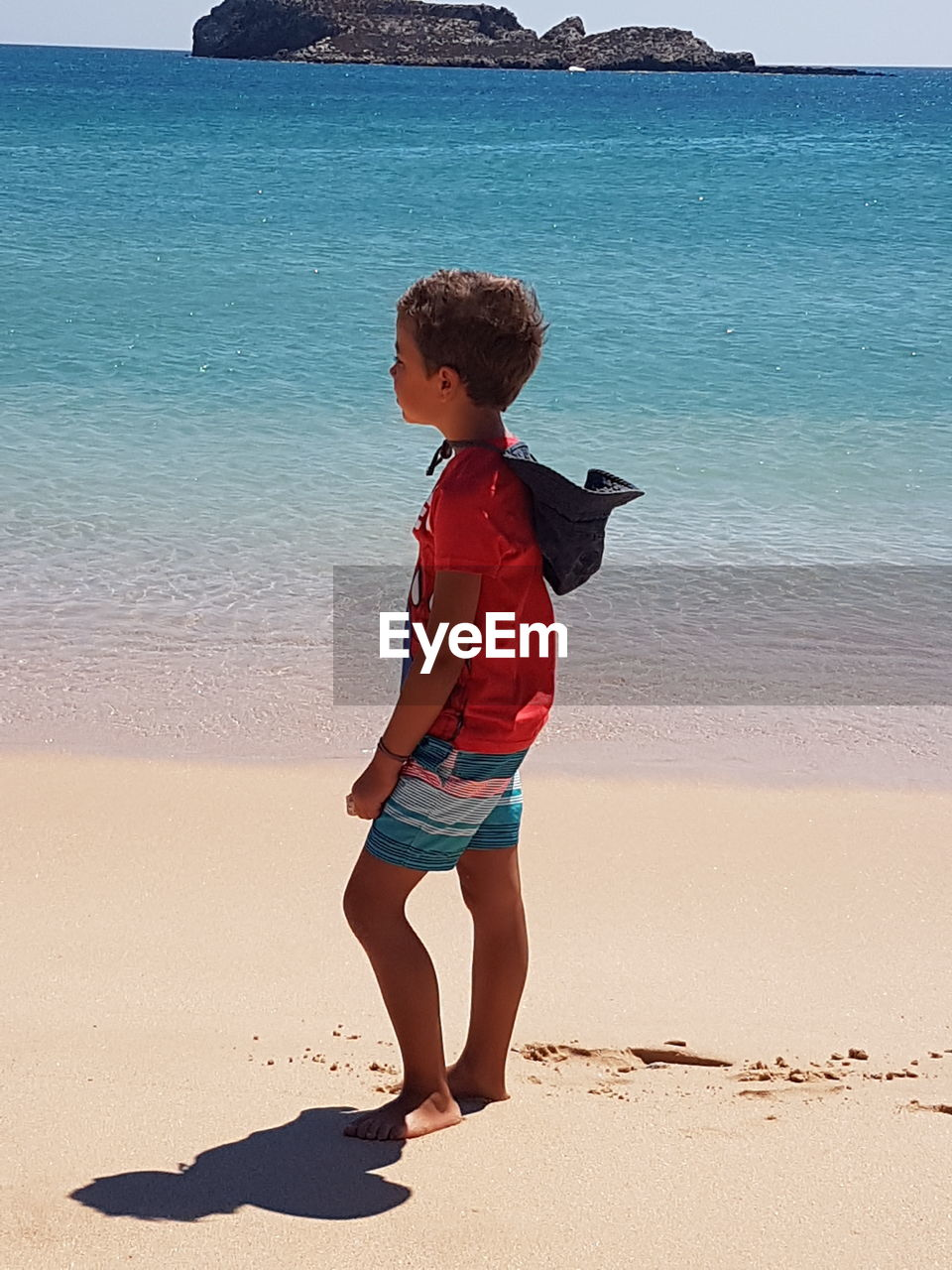Full length of boy standing on shore at beach