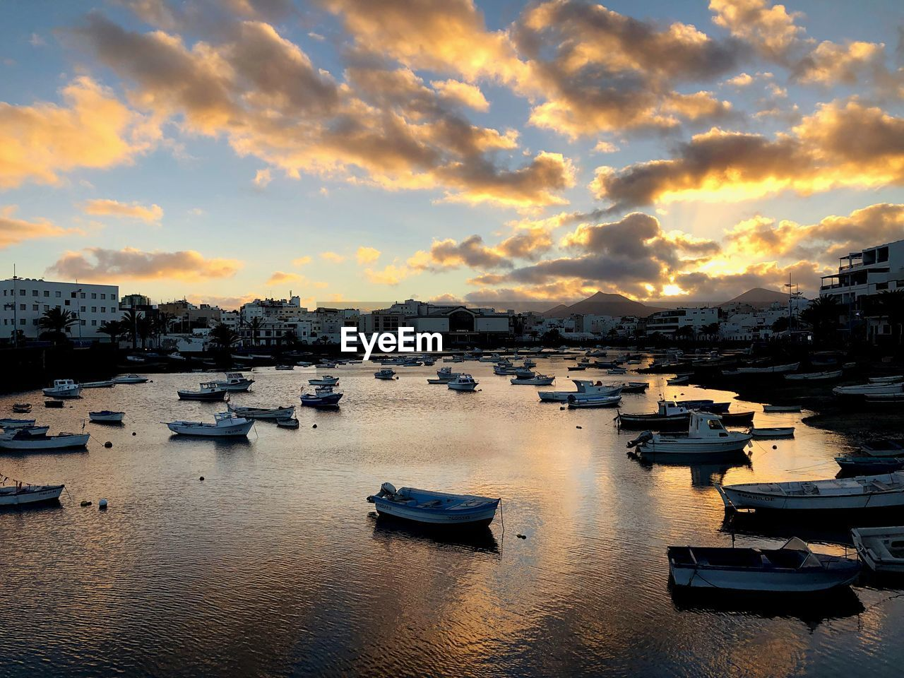 High angle view of sailboats moored at harbor during sunset