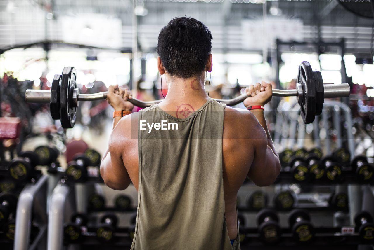 Rear View Of Man Exercising At Gym