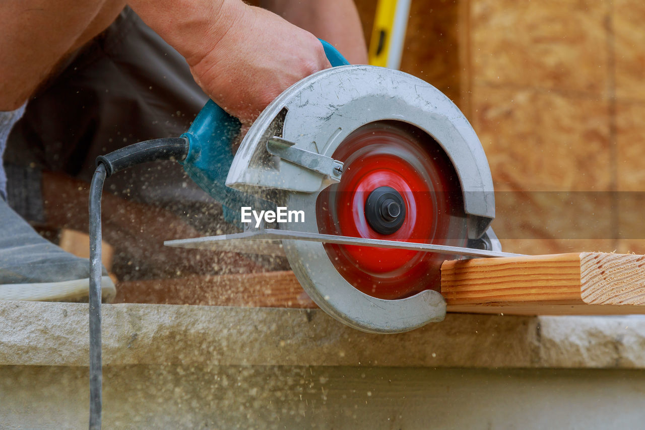 Low Section Of Male Carpenter Cutting Plank In Workshop