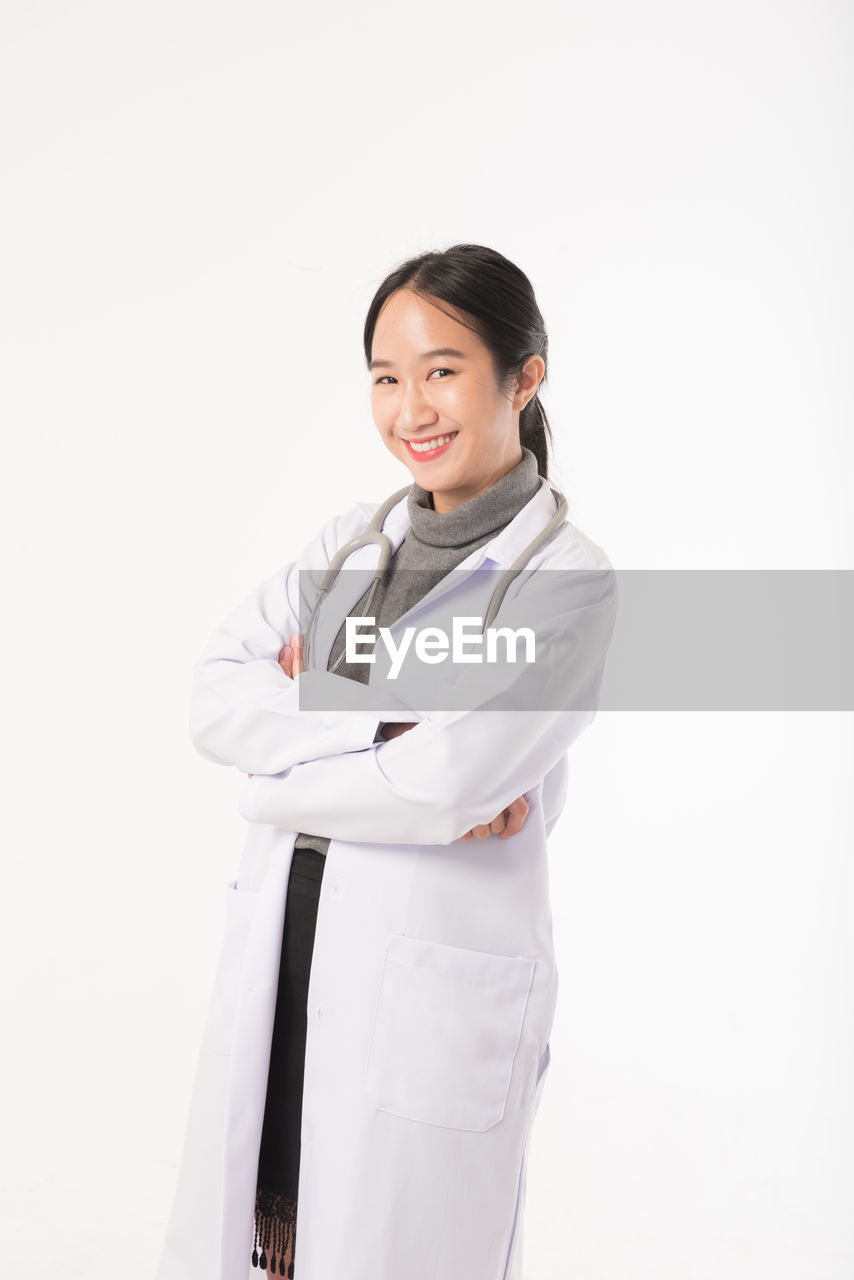 studio shot, smiling, one person, looking at camera, white background, indoors, occupation, clothing, portrait, standing, three quarter length, happiness, front view, female doctor, young adult, women, teeth, doctor, toothy smile, lab coat, uniform