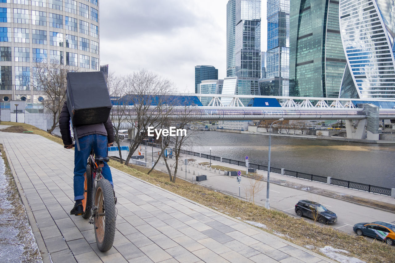 Food delivery service company by courier on bicycle near business center moscow city, moscow, russia