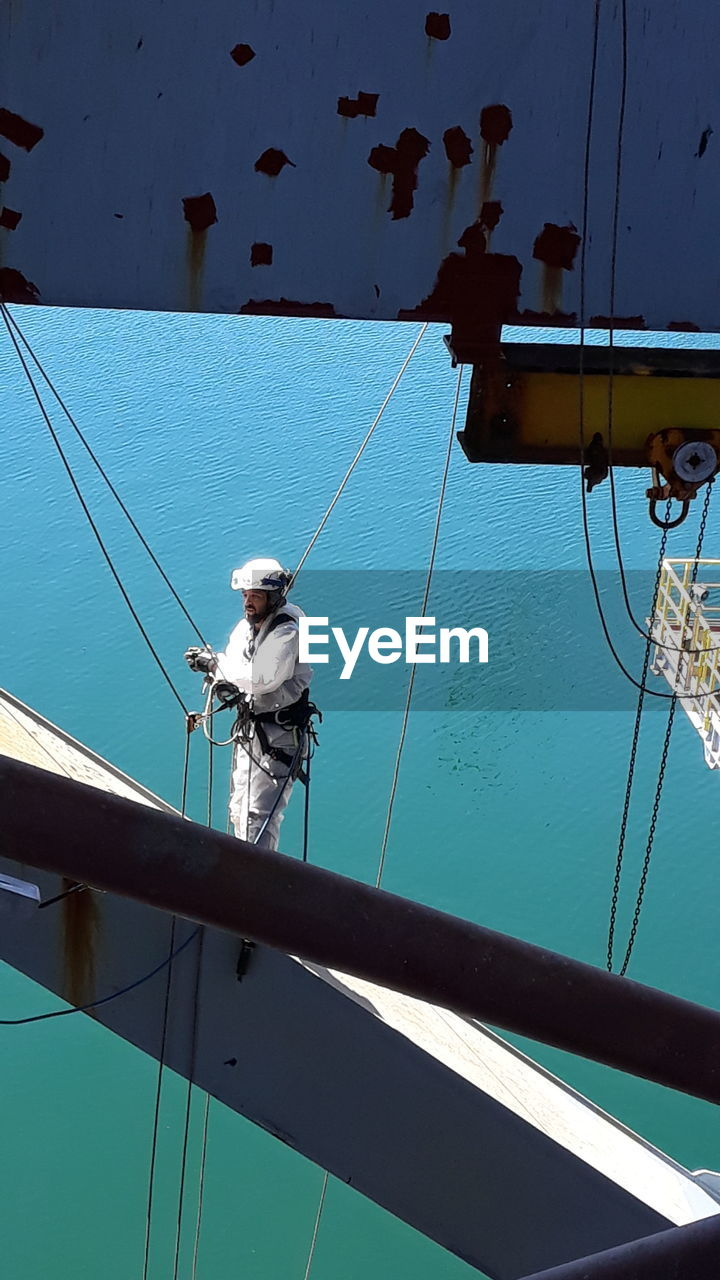 Worker On Boat Against Blue Sea