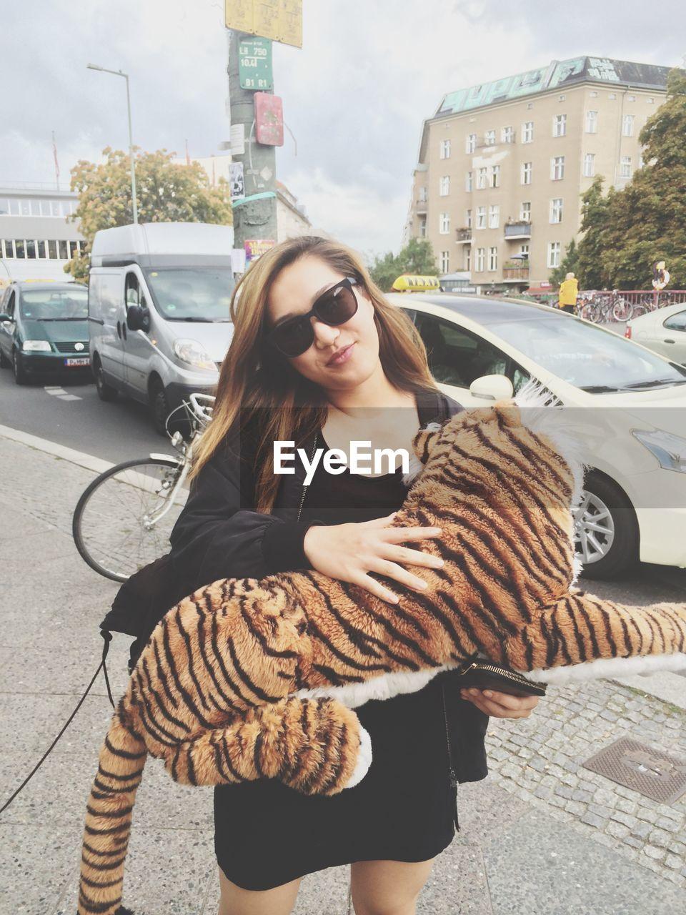 Portrait Of Woman Holding Tiger Stuffed Toy On Sidewalk
