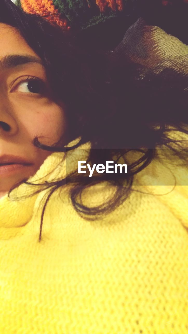 Cropped image of woman wearing yellow sweater