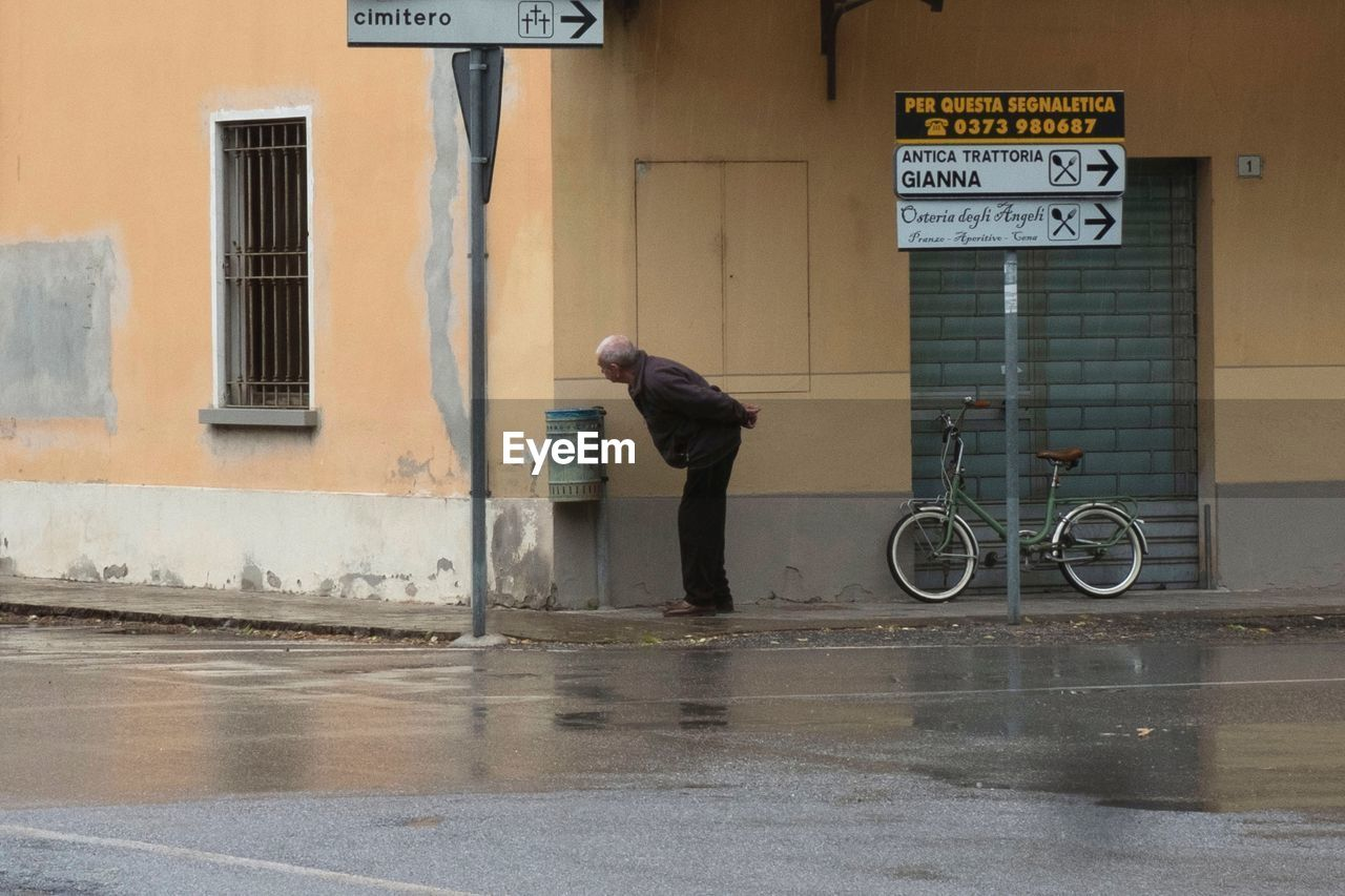 real people, one person, building exterior, built structure, architecture, city, text, full length, wet, street, lifestyles, communication, day, transportation, sign, casual clothing, side view, western script, men, rain, outdoors, rainy season