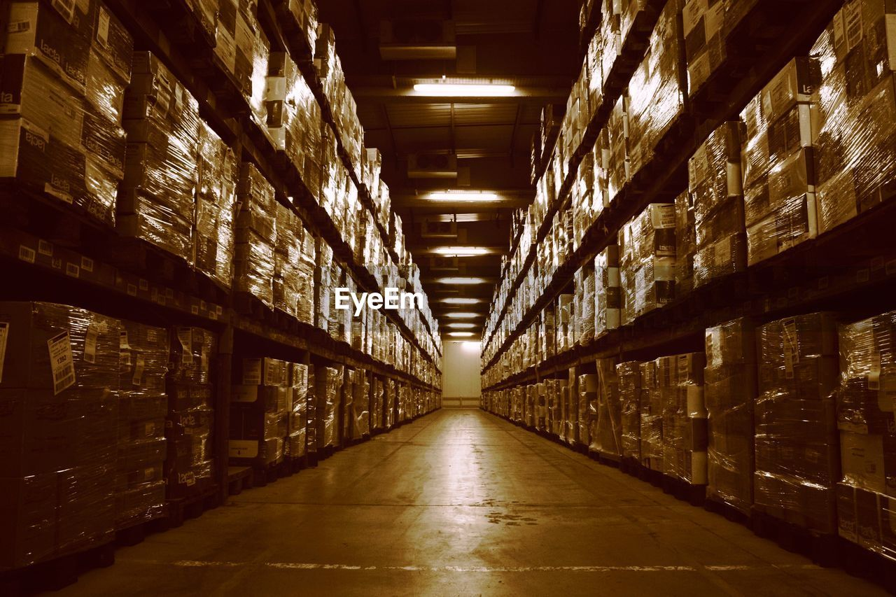 architecture, building, indoors, illuminated, warehouse, shelf, the way forward, domestic room, arcade, direction, corridor, diminishing perspective, in a row, no people, built structure, lighting equipment, large group of objects, storage compartment, container, business, aisle, alley, ceiling, long