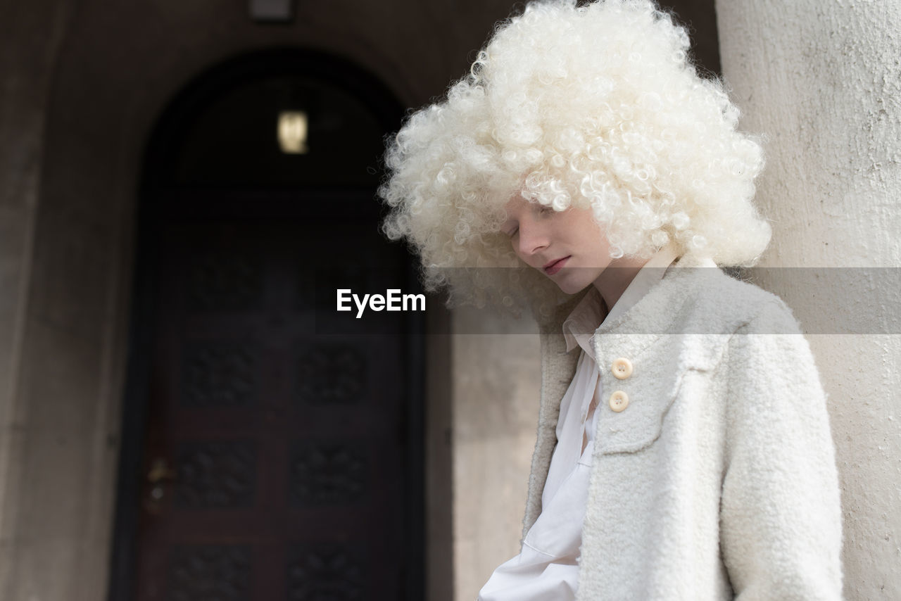 Young woman wearing curly hair wig outside house