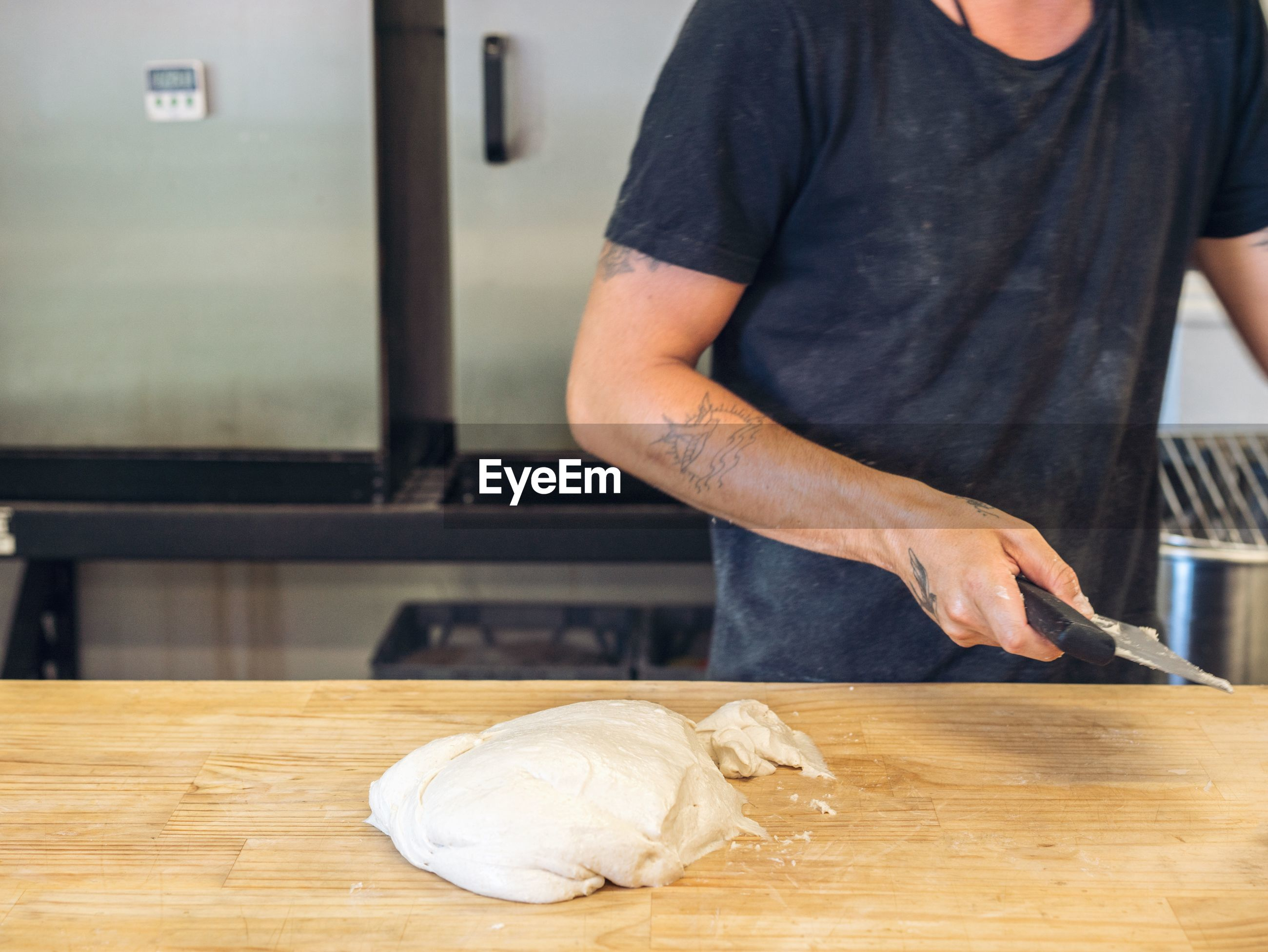 Midsection of man preparing food making bread at table