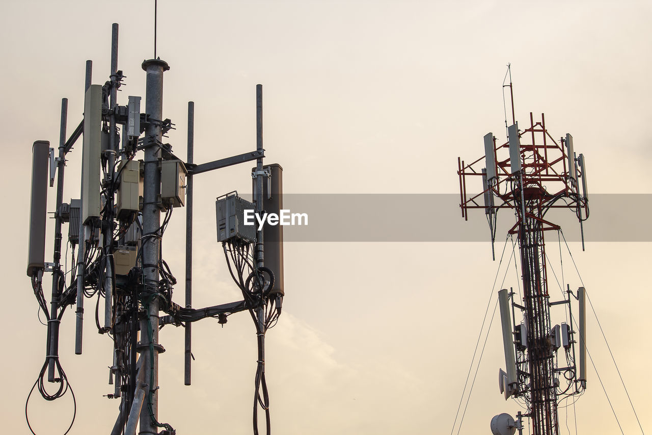 sky, technology, connection, no people, low angle view, communication, nature, outdoors, fuel and power generation, metal, lighting equipment, electricity, day, cable, industry, focus on foreground, electricity pylon, tall - high, broadcasting, sunset